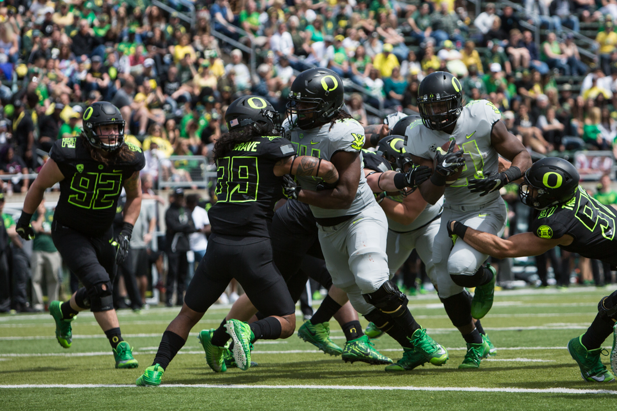 Team Free running back Royce Freeman (#21) powers through several defenders. The 2017 Oregon Ducks Spring Game provided fans their first look at the team under new Head Coach Willie Taggart's direction.  Team Free defeated Team Brave 34-11 on a sunny day at Autzen Stadium in Eugene, Oregon.  Photo by Austin Hicks, Oregon News Lab