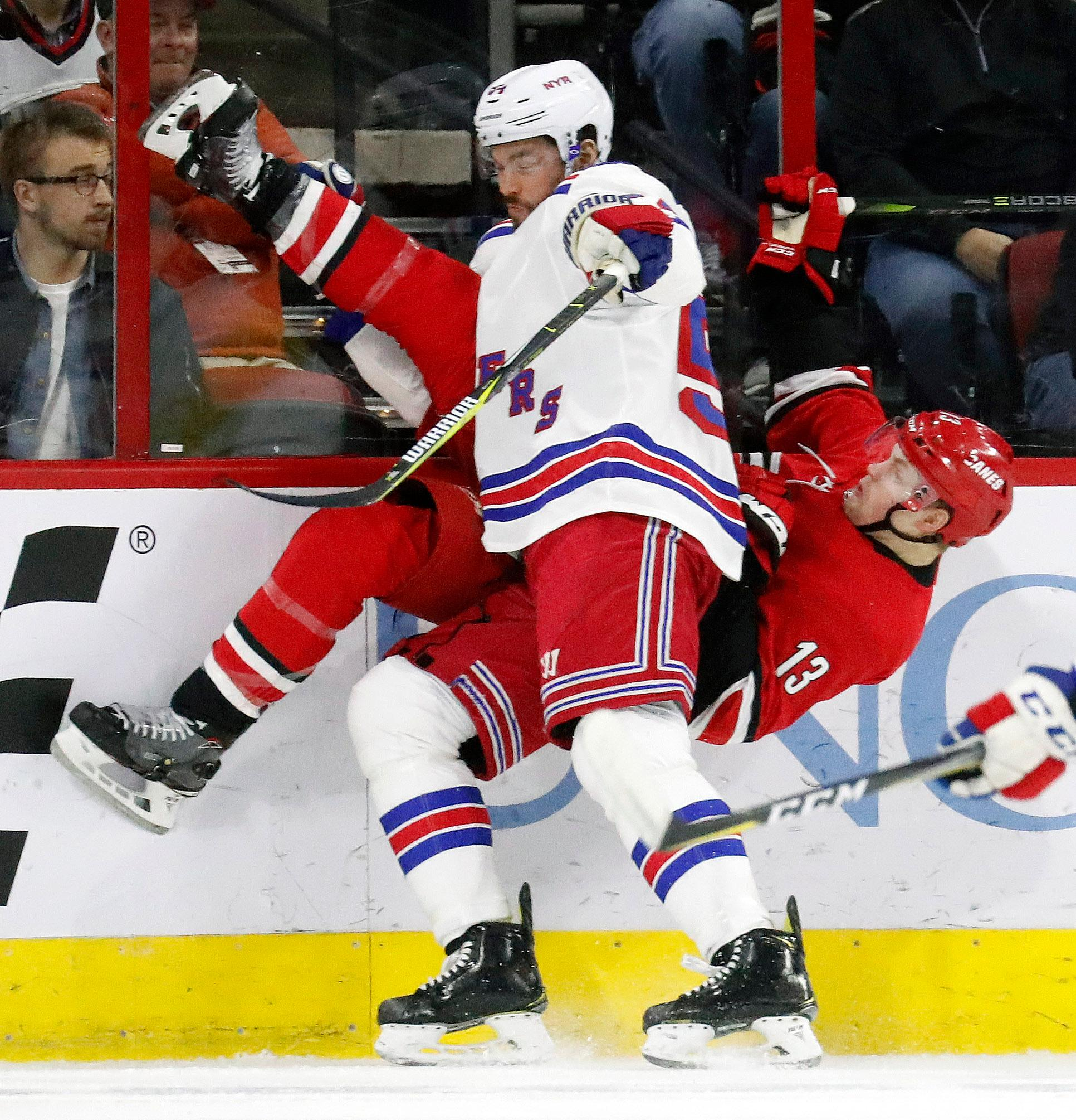 Carolina Hurricanes' Warren Foegele (13) and New York Rangers' Adam McQuaid (54) collide along the boards during the first period of an NHL hockey game in Raleigh, N.C., Tuesday, Feb. 19, 2019. (AP Photo/Chris Seward)