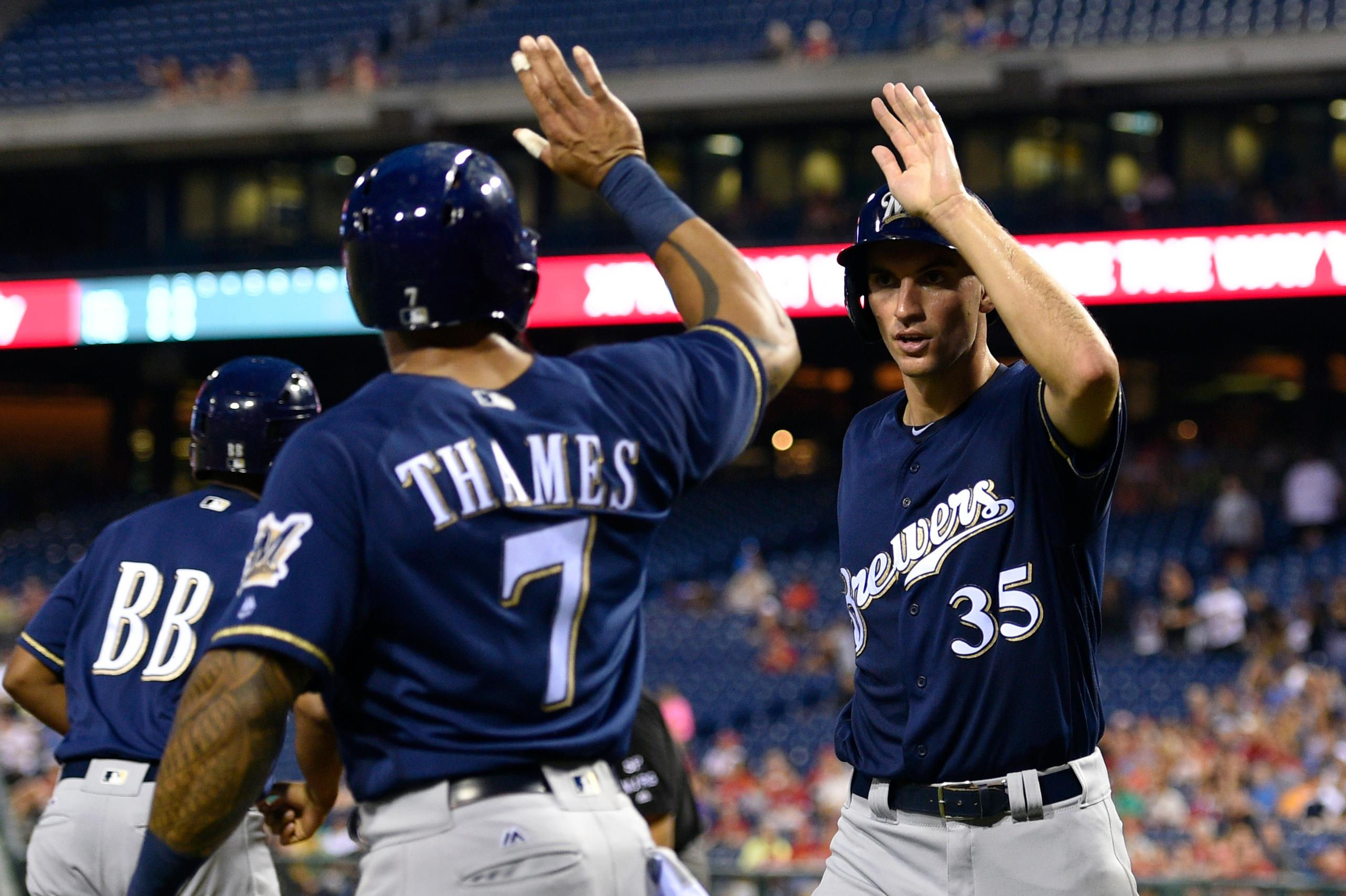 Milwaukee Brewers' Brent Suter, right, high-fives Eric Thames (7) after scoring on a Ryan Braun double during the third inning against the Philadelphia Phillies, Saturday, July 22, 2017, in Philadelphia. (AP Photo/Derik Hamilton)