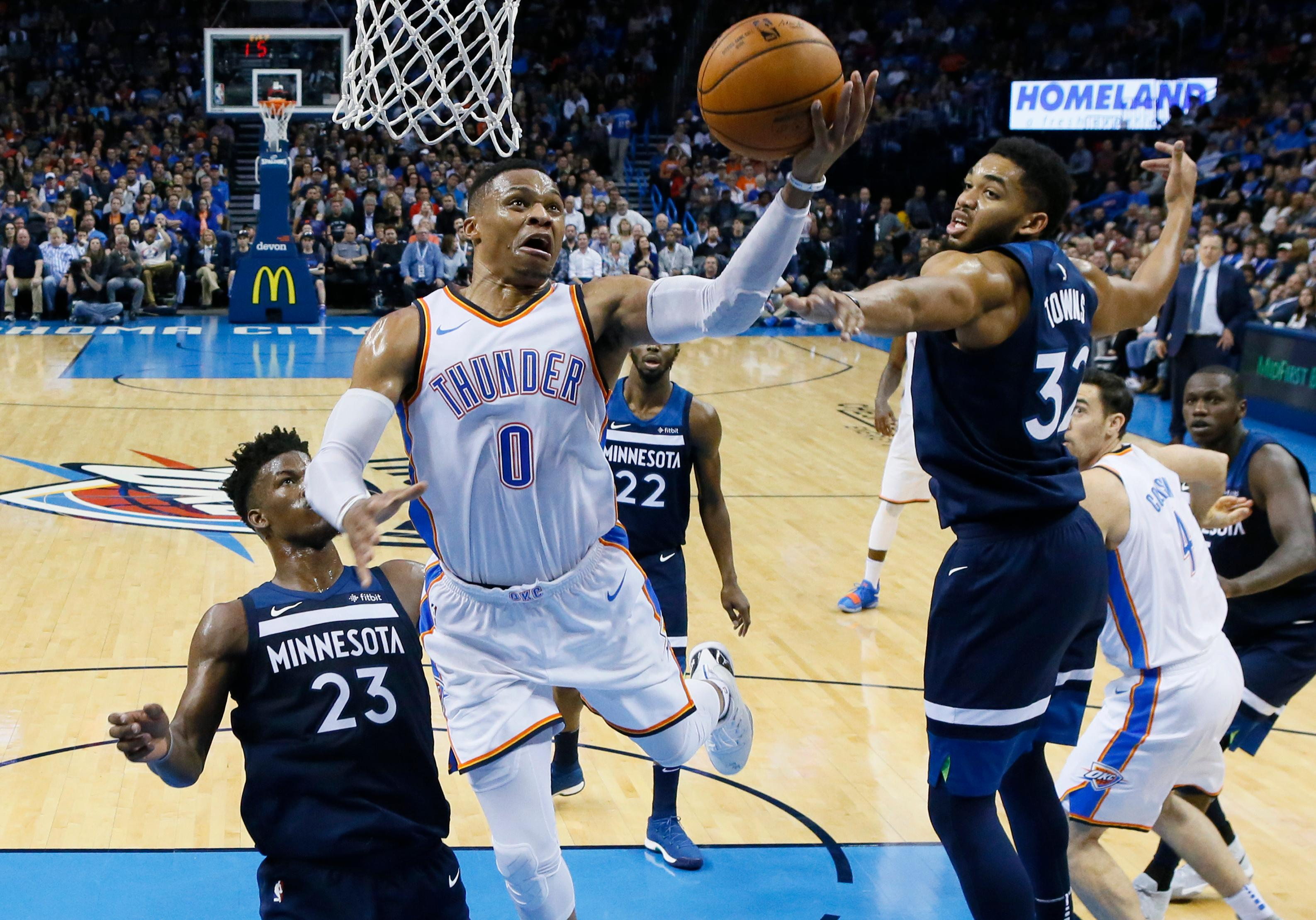 Oklahoma City Thunder guard Russell Westbrook (0) shoots between Minnesota Timberwolves guard Jimmy Butler (23) and center Karl-Anthony Towns during the second quarter of an NBA basketball game in Oklahoma City, Friday, Dec. 1, 2017. (AP Photo/Sue Ogrocki)