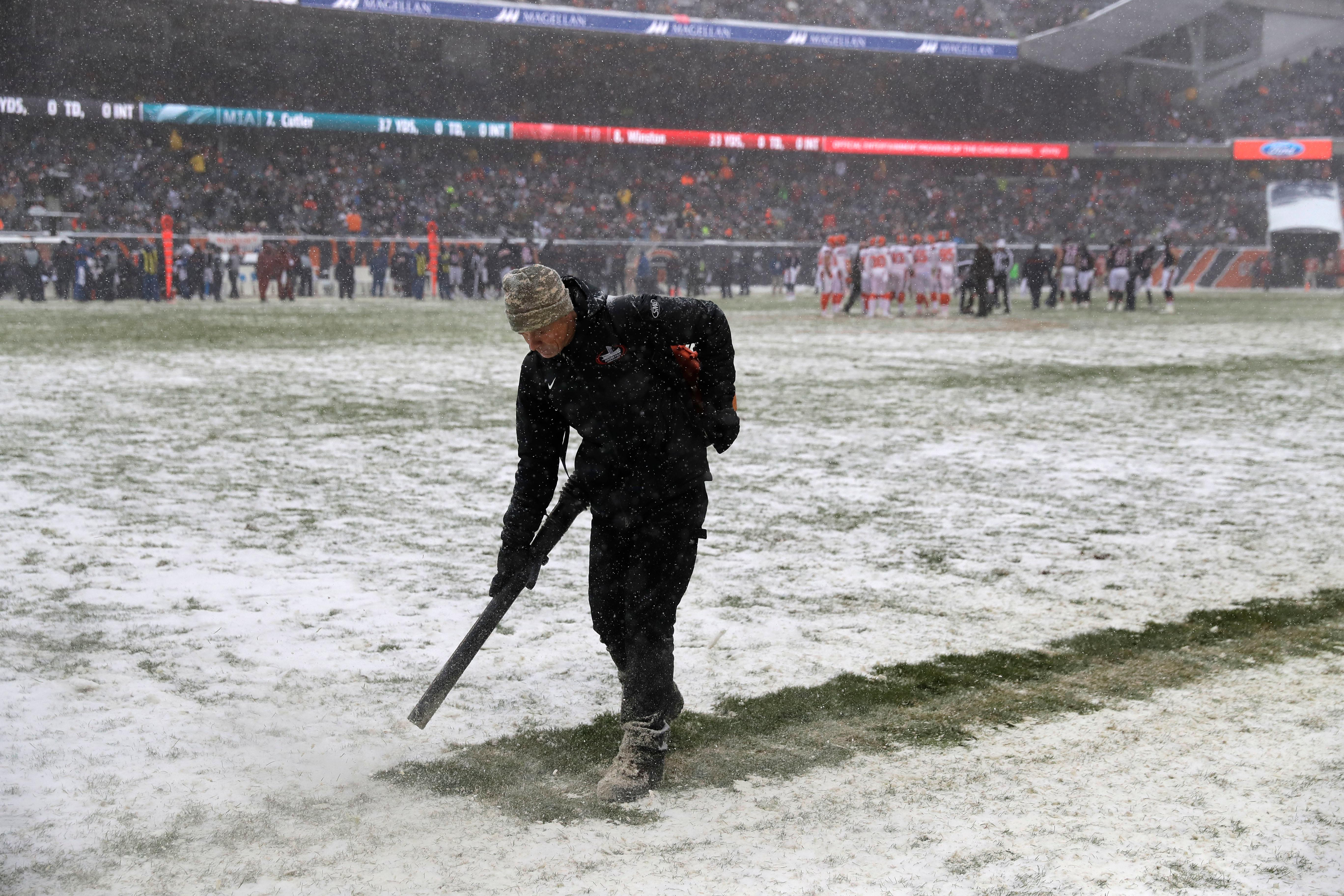 A worker clears snow from field lines at Soldier Field during an NFL football game between the Chicago Bears and Cleveland Browns in Chicago, Sunday, Dec. 24, 2017. (AP Photo/Charles Rex Arbogast)