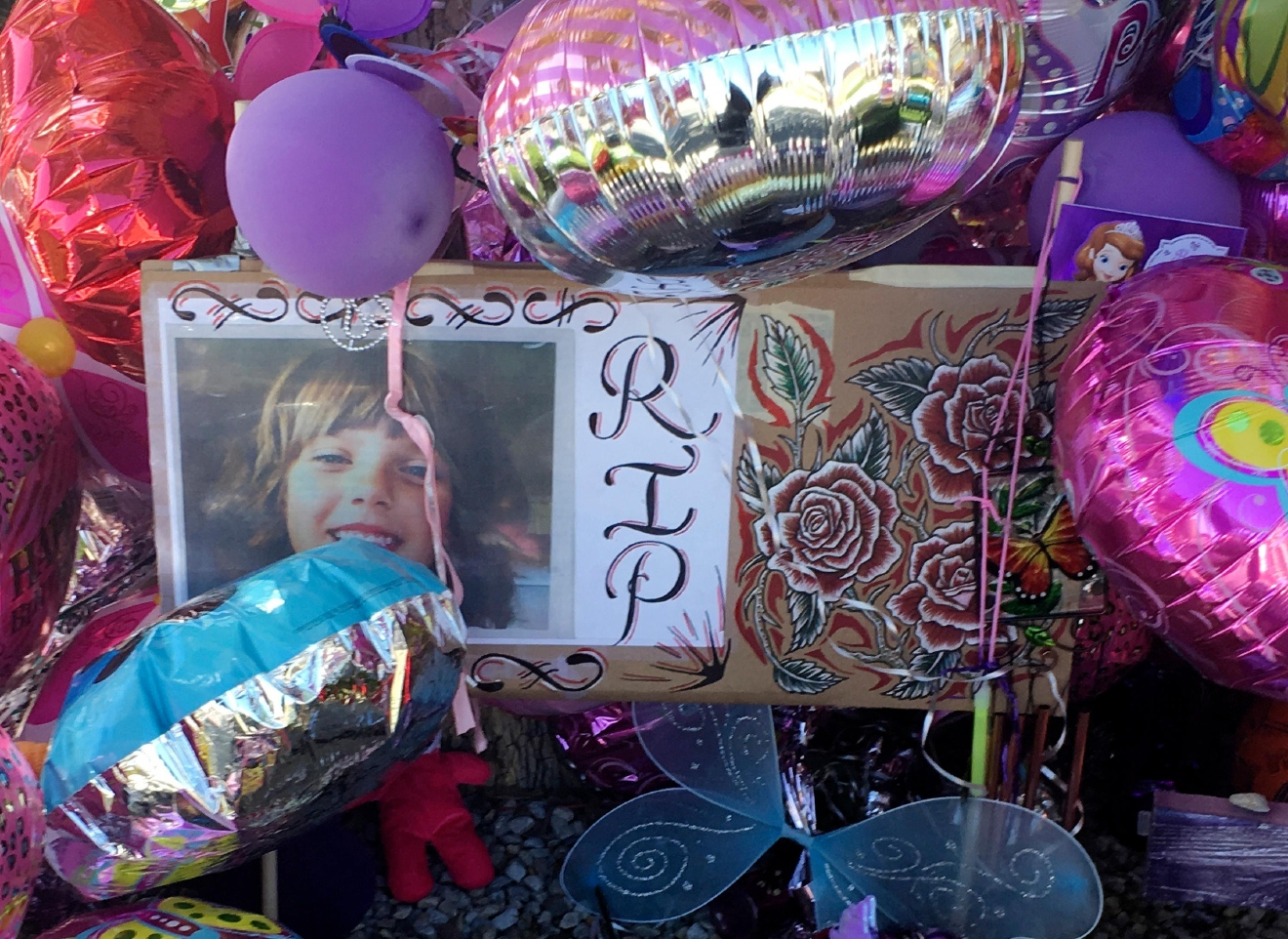 A picture of Victoria Martens, a 10-year-old Albuquerque girl brutally murdered last week, is placed in a memorial outside her former Albuquerque apartment on Monday, Aug. 29, 2016.  (AP Photo/Russell Contreras)
