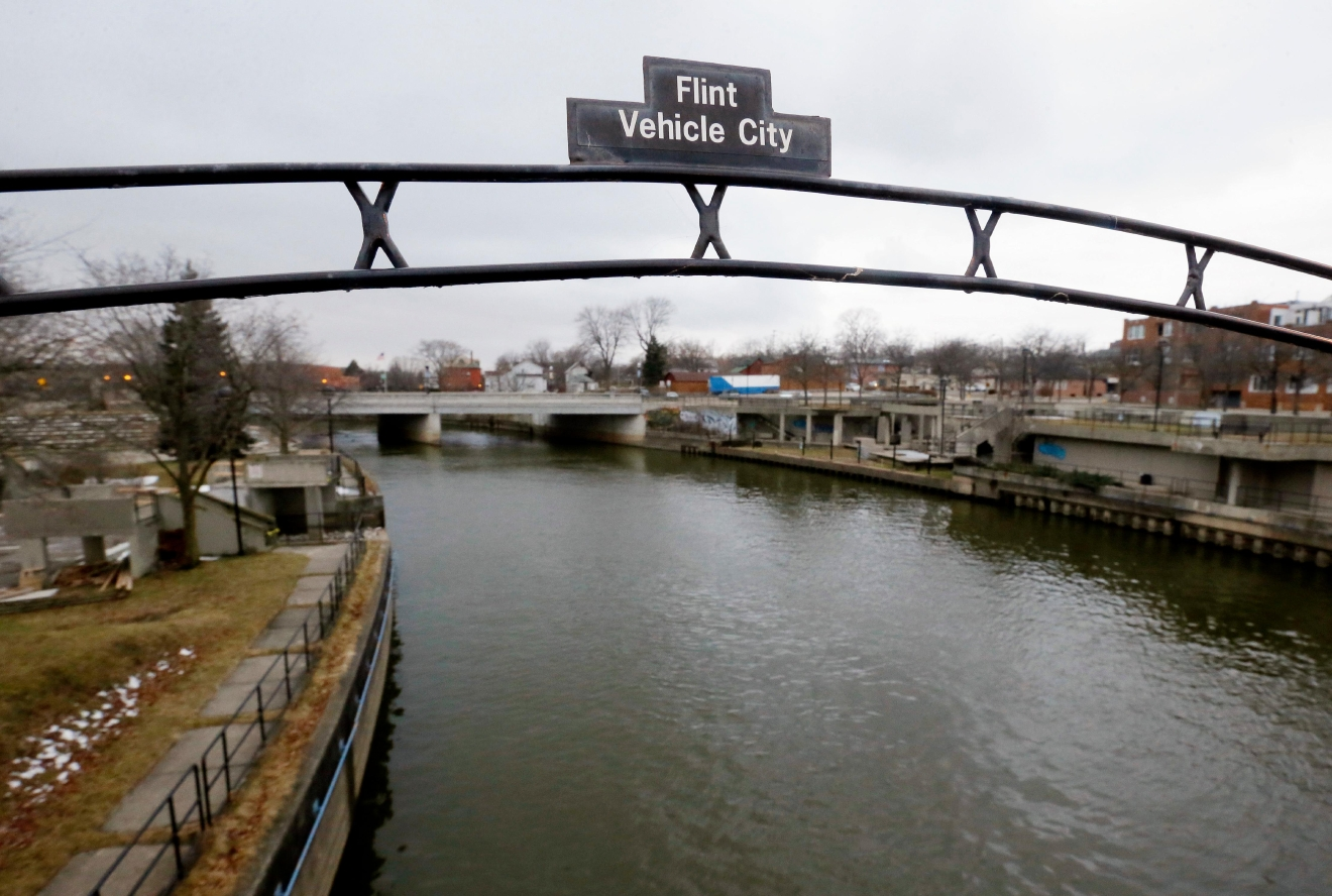 FILE - This Jan. 26, 2016, file photo shows a sign over the Flint River in Flint, Mich. Virginia Tech researchers who exposed the lead-tainted water problem in Flint, said Thursday, Aug. 11, 2016, the city's water quality has greatly improved, based on tests at more than 160 homes. (AP Photo/Carlos Osorio, File)