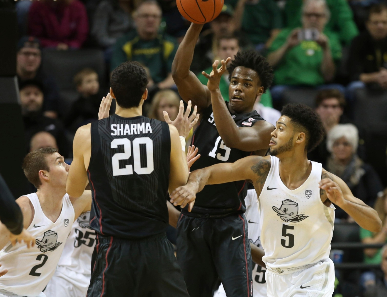 Stanford's Marcus Allen, center, passes to teammate Josh Sharma, center left, under pressure from Oregon's Casey Benson, left, and Tyler Dorsey, right, during the first half an NCAA college basketball game Saturday, Jan. 21, 2017, in Eugene, Ore. (AP Photo/Chris Pietsch)