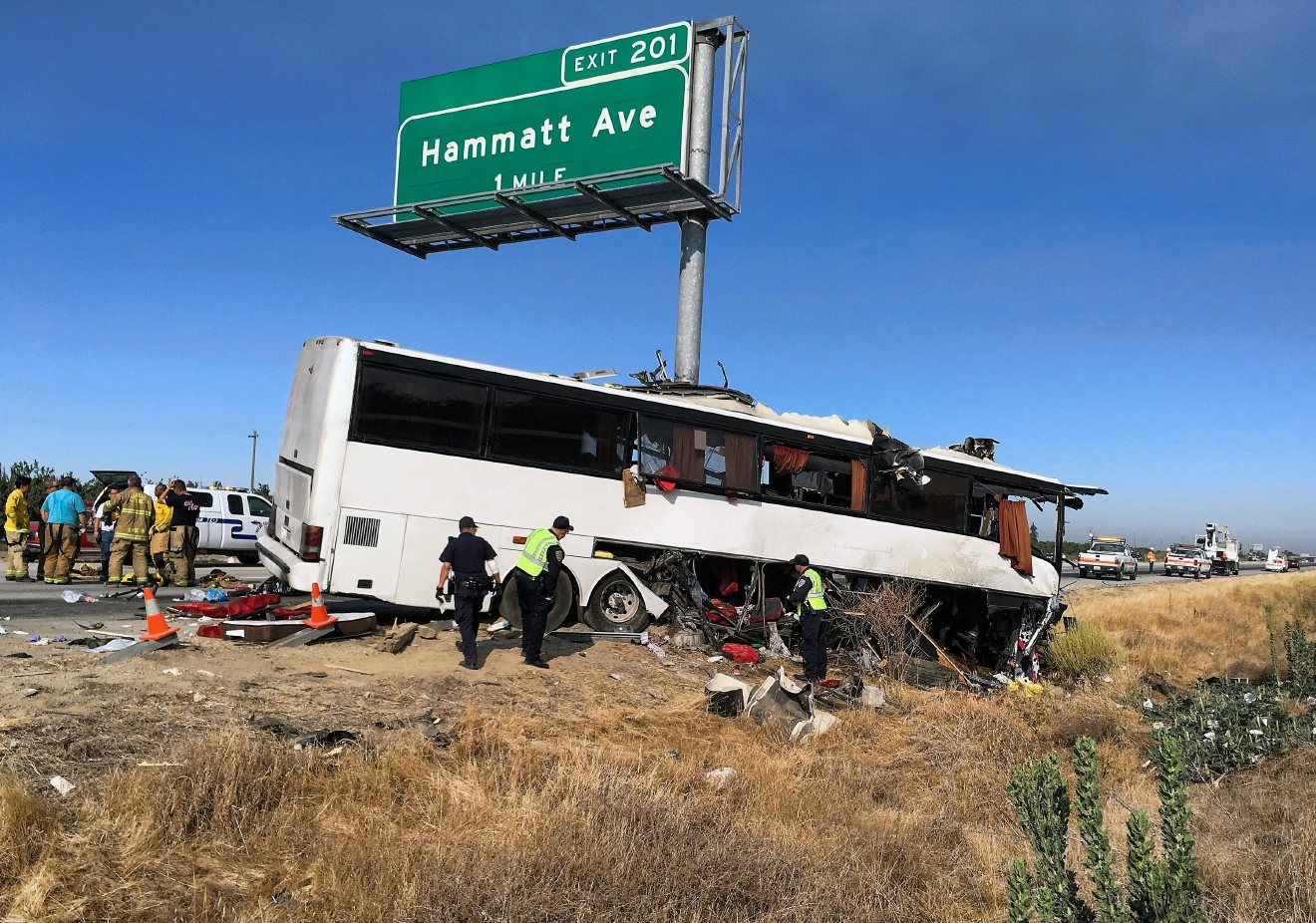 Authorities investigate the scene of a charter bus crash on northbound Highway 99 between Atwater and Livingston, Calif., Tuesday, Aug. 2, 2016. A charter bus veered off a central California freeway before dawn Tuesday and struck a pole that sliced the vehicle nearly in half, killing mulitple people and sending at least five others to hospitals, authorities said. (AP Photo/Scott Smith)