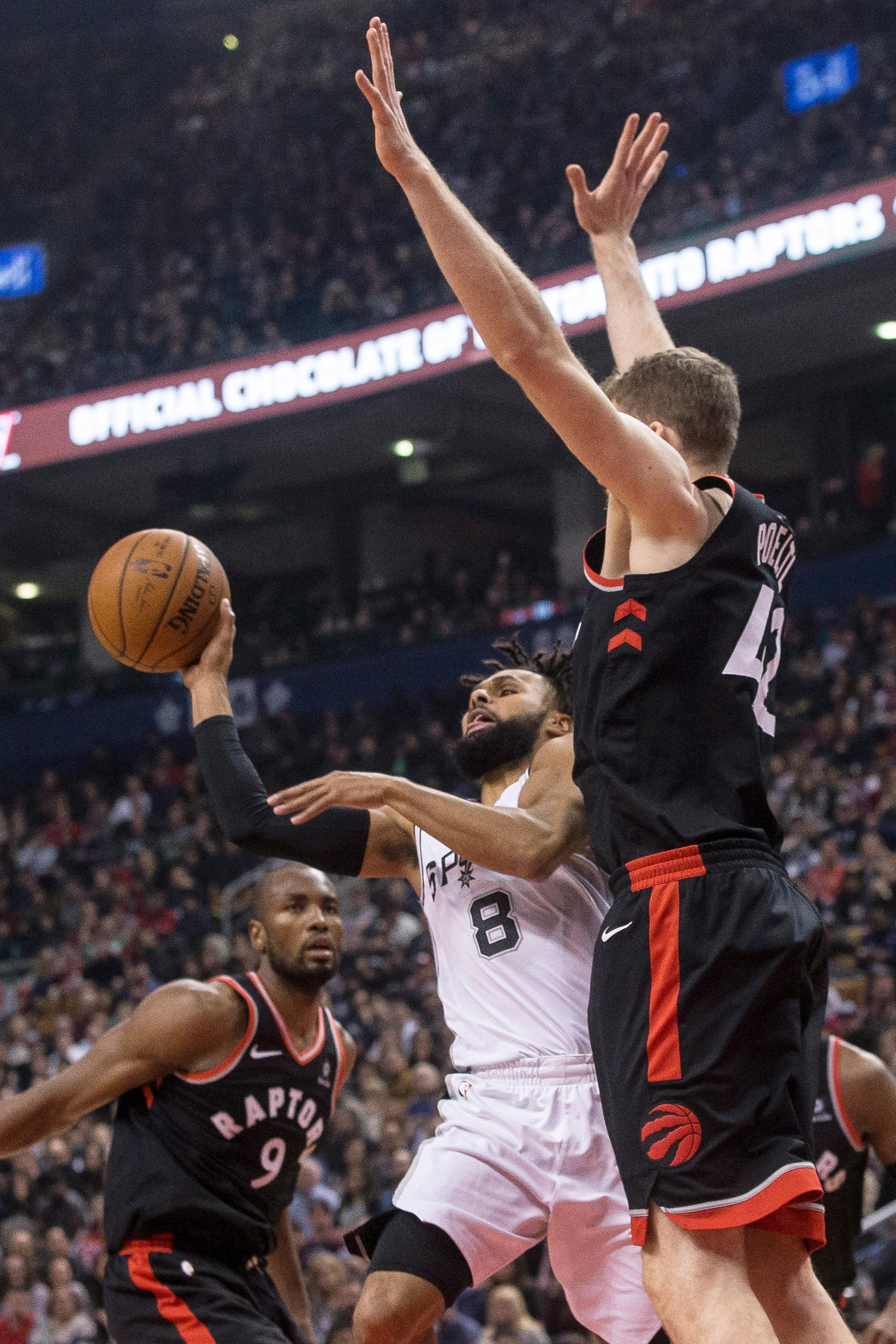 San Antonio Spurs guard Patty Mills (8) passes the ball as Toronto Raptors centrer Jakob Poeltl (42) defends during the first half of an NBA basketball game Friday, Jan. 19, 2018, in Toronto. (Chris Young/The Canadian Press via AP)