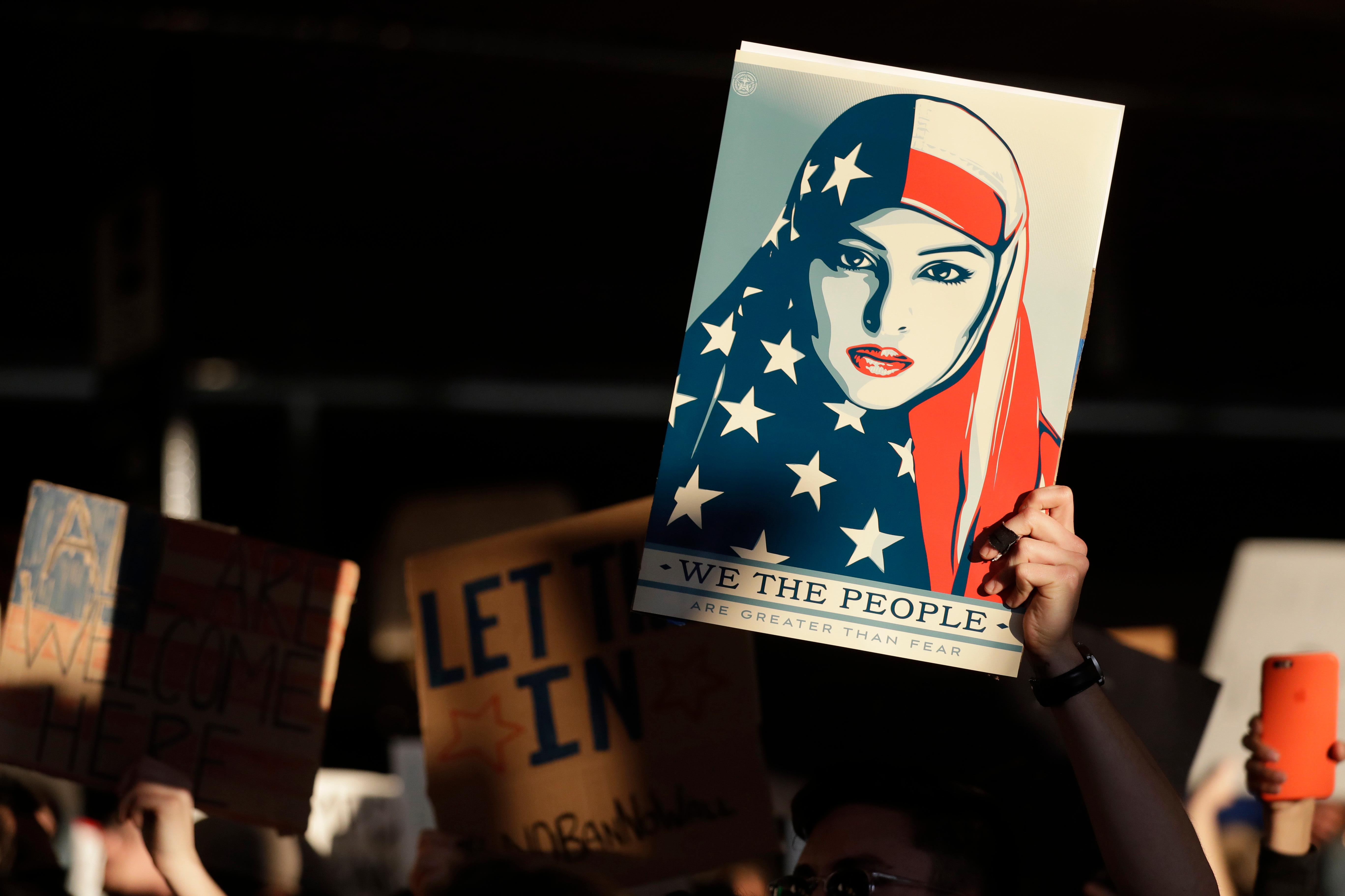 FILE - In this Jan. 28, 2017, file photo a protester holds a sign at San Francisco International Airport during a demonstration to denounce President Donald Trump's executive order that bars citizens of seven predominantly Muslim-majority countries from entering the U.S. (AP Photo/Marcio Jose Sanchez, File)