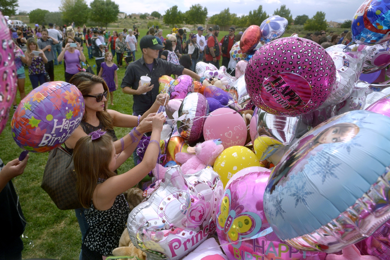 In a Sunday, Aug. 28, 2016 photo, Stephanie Duneman and her daughter Isabella Duneman, 9, tie up balloons they brought to celebrate the birthday of Victoria Martens in Mariposa Basin Park, in Albuquerque. (Greg Sorber/Albuquerque Journal via AP)