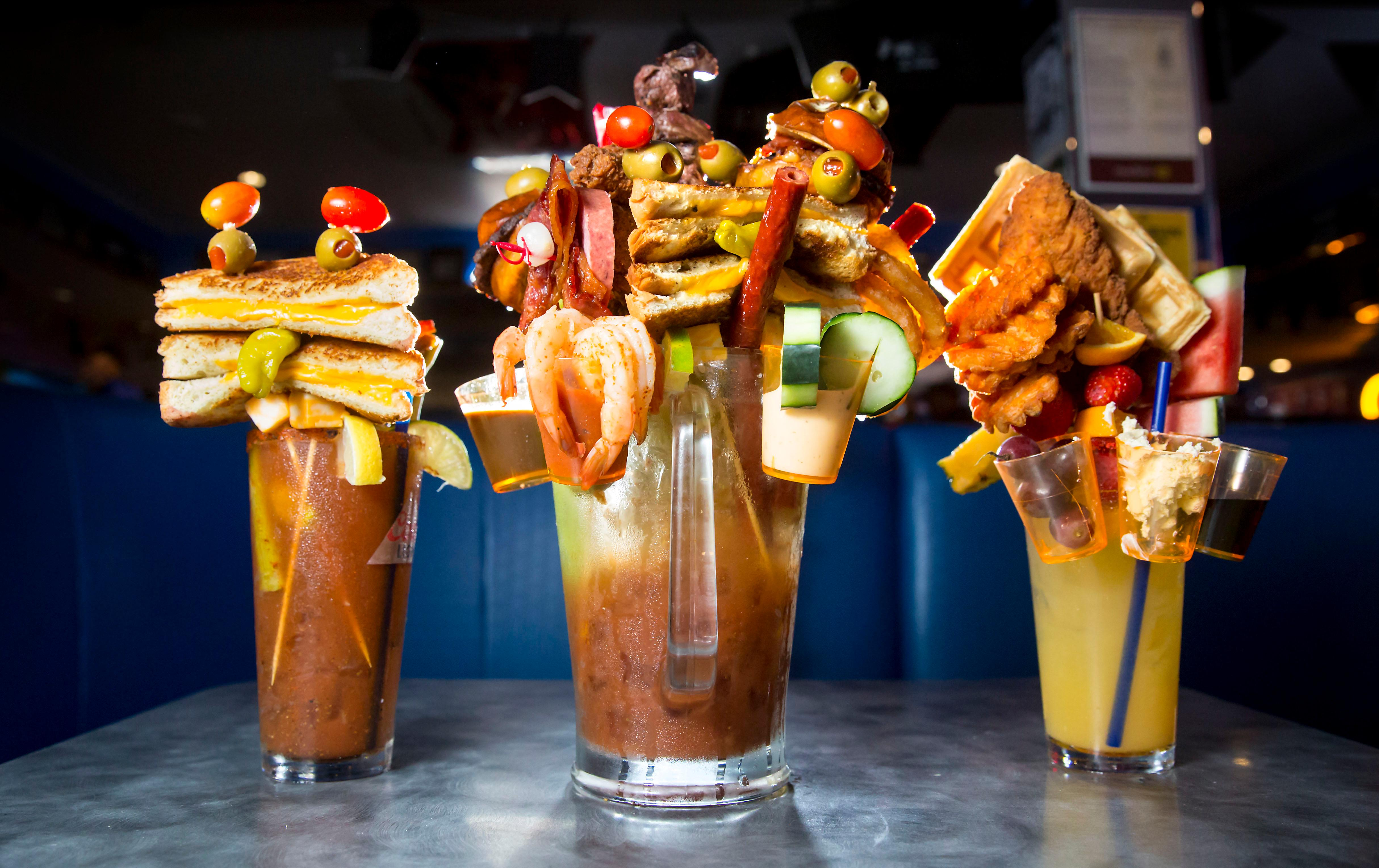 The Southern Bloody Mary (Chicken and Waffles, 22oz Manmosa Base), The Grilled Cheese (22oz Bloody Mary with Grilled Cheese Sandwich and the Big Mother Mary (Full pitcher of bloody mary, grilled cheese sandwich, steak bites, ribs, salami, olives, sliders, onion rings, shrimp cocktail, fried shrimp, cucumber, candied bacon bows, and meat stick straws). The Big Mother Mary HAS to be shared by two people. The Garage Bar &amp;amp; Grill in Bremerton, WA. (Sy Bean / Seattle Refined)<p></p>