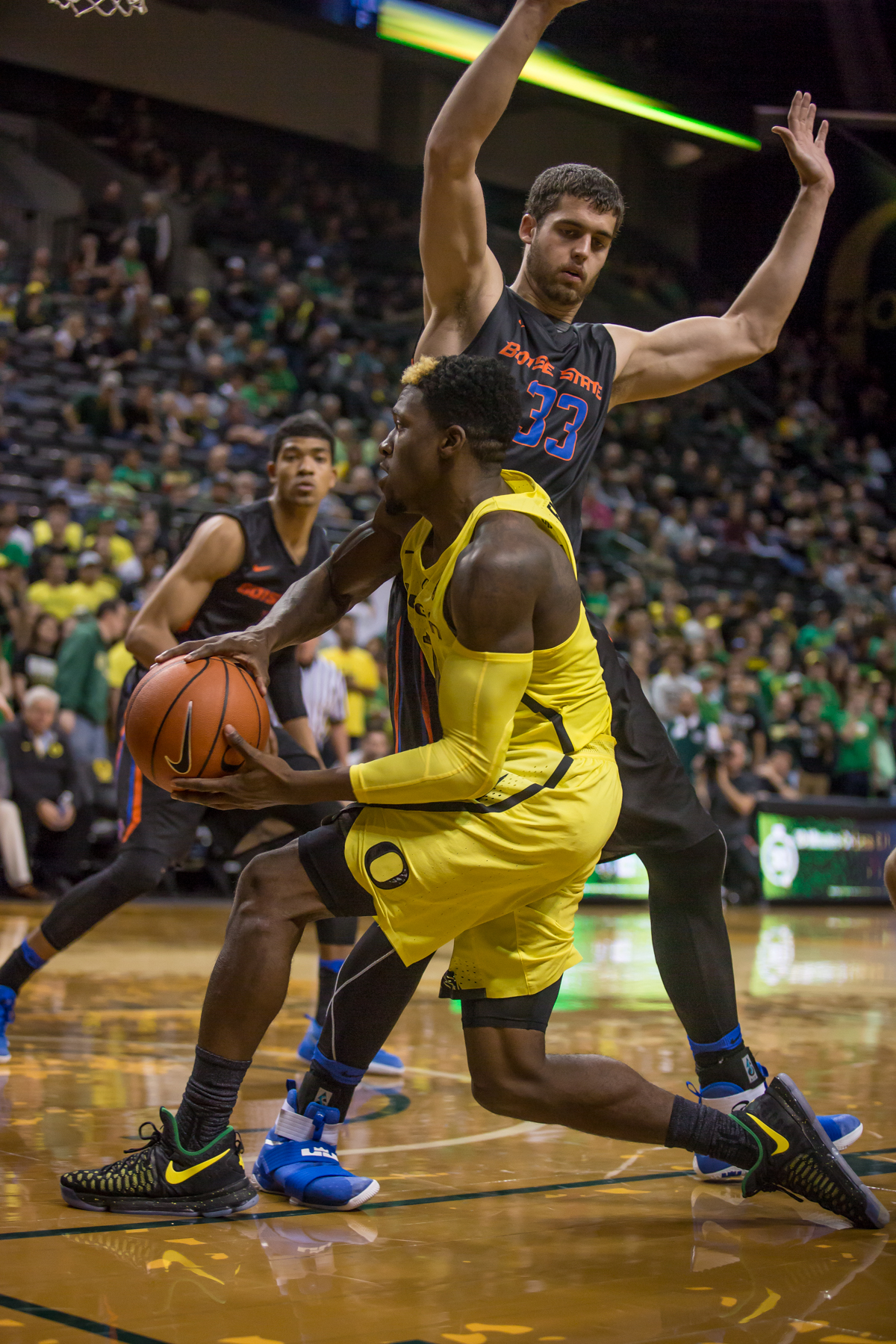 Oregon guard Dylan Ennis (#31) passes the ball around Boise State forward David Wacker (#33). After trailing for most of the game, the Oregon Ducks defeated the Boise State Broncos 68-63. Photo by Dillon Vibes