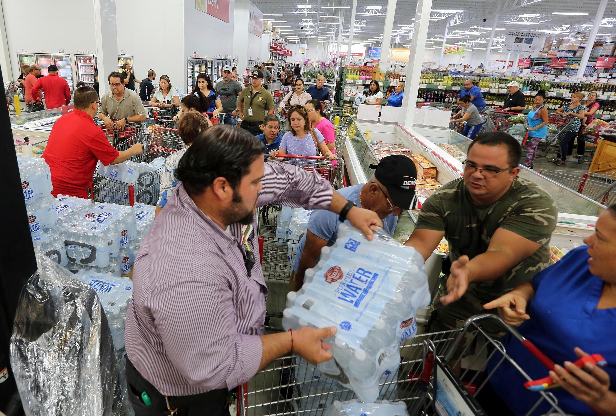 FILE- This Sept. 5, 2017 file photo shows residents in a long line waiting to purchase water at BJ Wholesale in preparation for Hurricane Irma in Miami. Roberto Koltun/Miami Herald via AP, File)