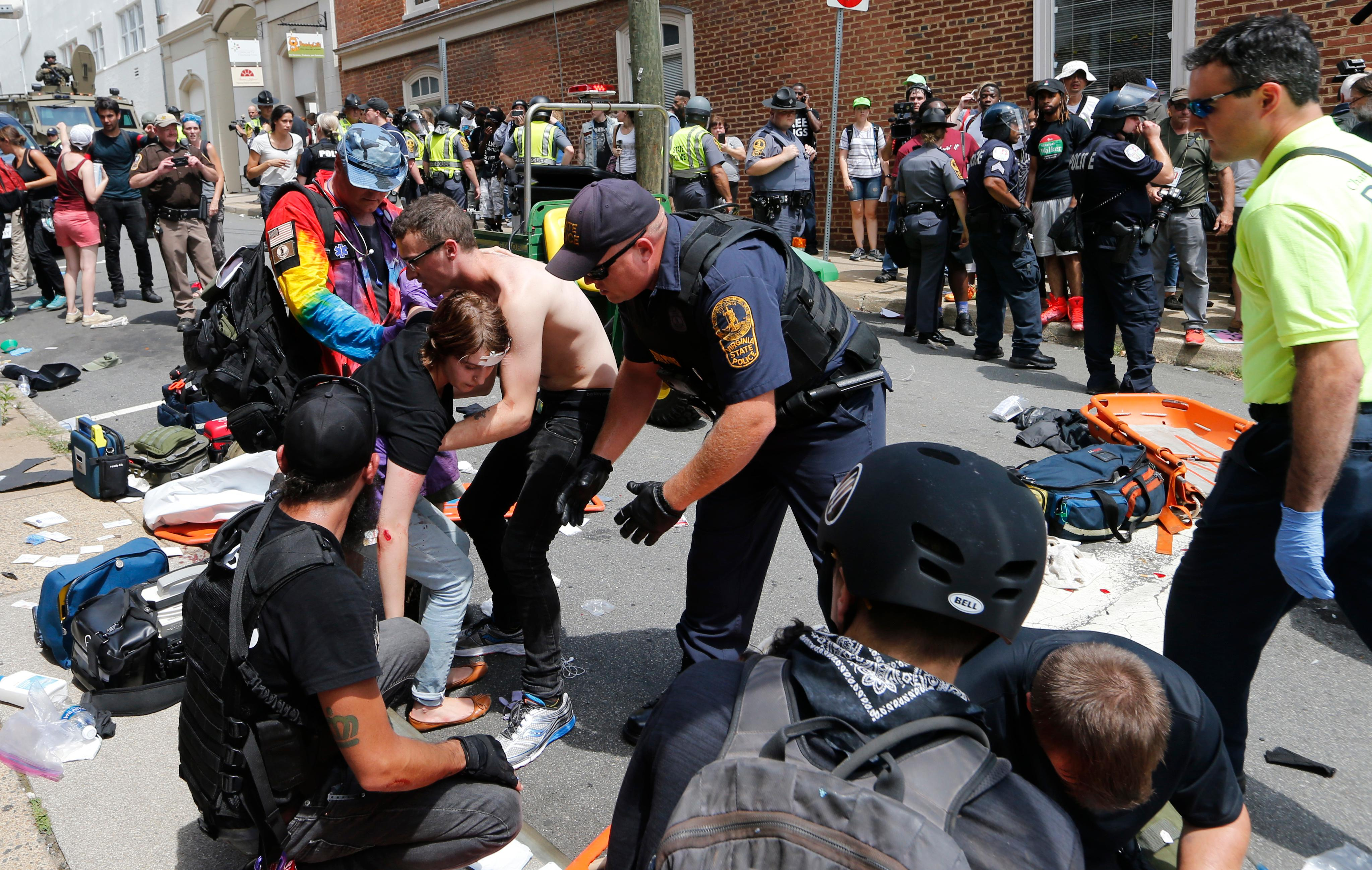 Rescue personnel help injured people after a car ran into a large group of protesters after a white nationalist rally in Charlottesville, Va., Saturday, Aug. 12, 2017. The nationalists were holding the rally to protest plans by the city of Charlottesville to remove a statue of Confederate Gen. Robert E. Lee. There were several hundred protesters marching in a long line when the car drove into a group of them. (AP Photo/Steve Helber)