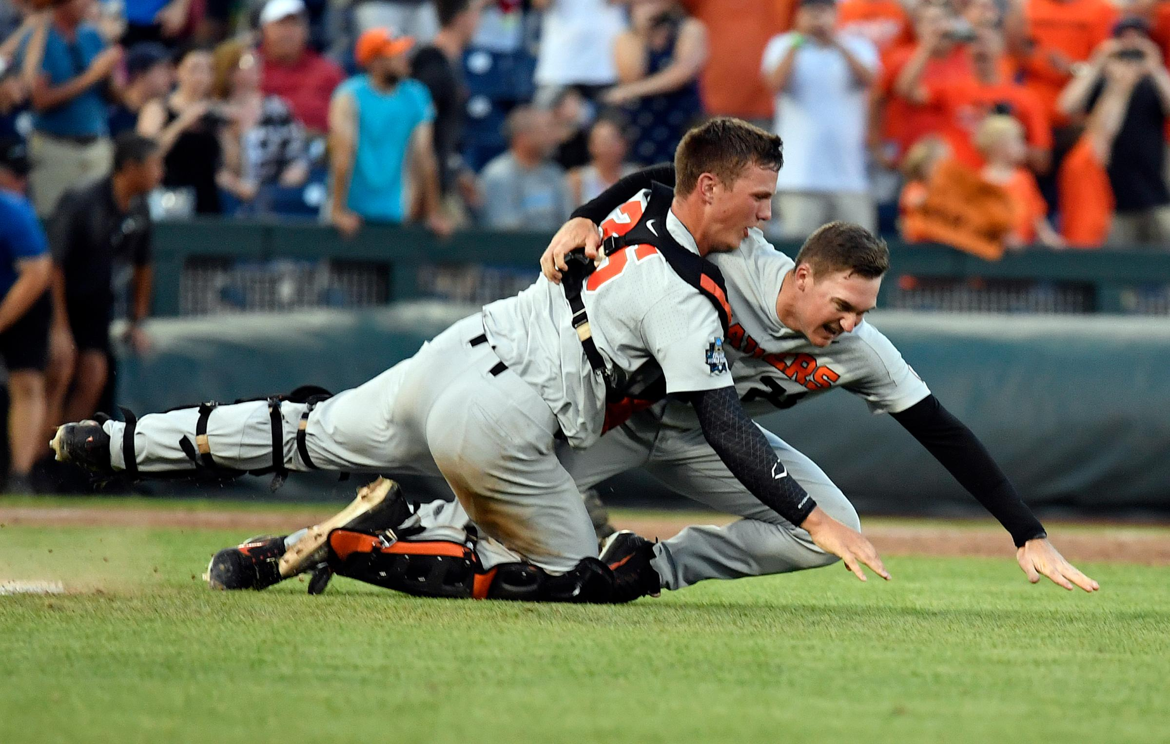 Oregon State's Adley Rutschman, left, tackles Kevin Abel, right, as they celebrate after winning Game 3 of the NCAA College World Series baseball finals in Omaha, Neb., Thursday, June 28, 2018. Oregon State defeated Arkansas 5-0. (AP Photo/Ted Kirk)