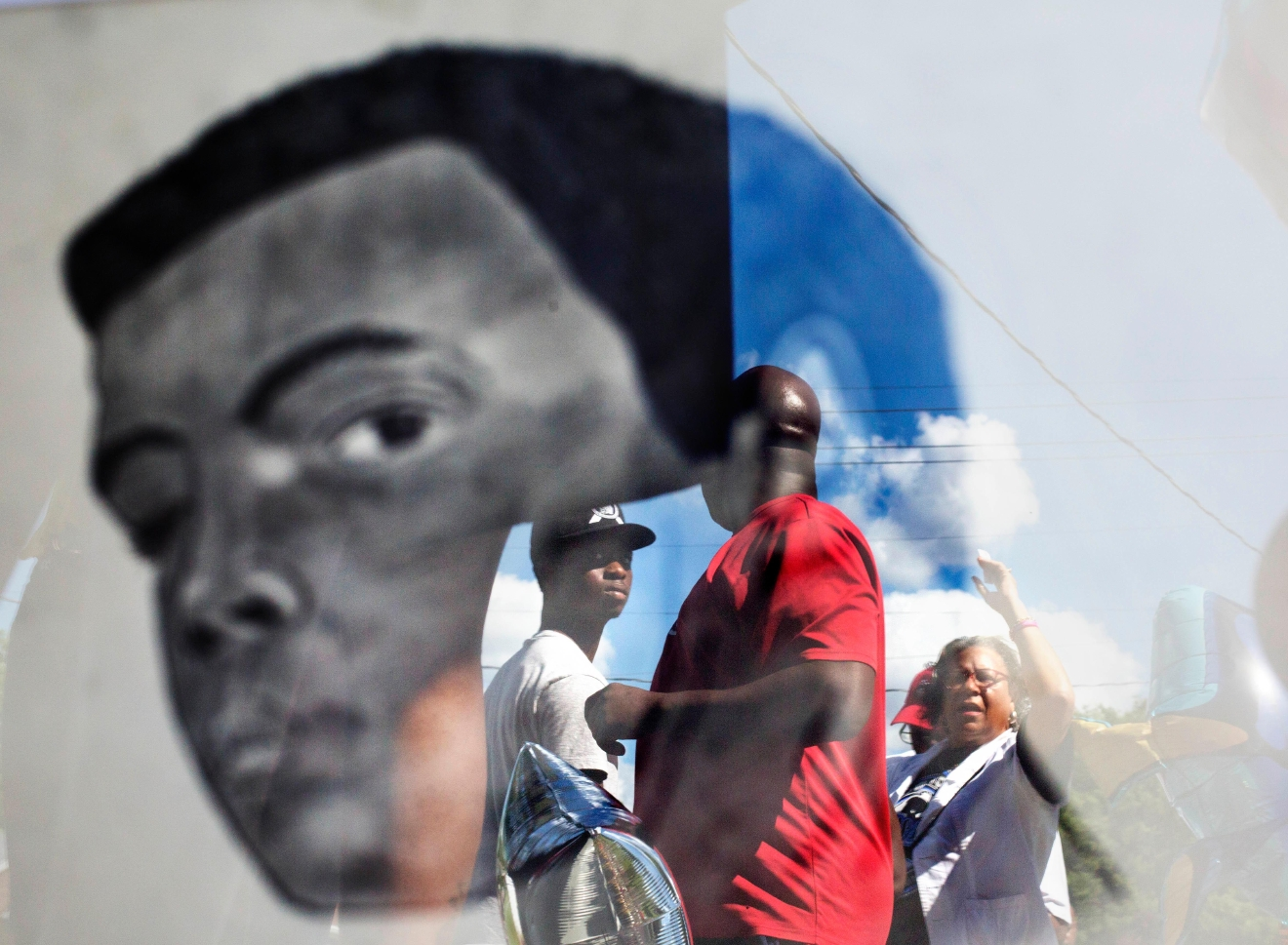 A crowd is reflected in a sketch of Muhammad Ali on the front porch of his childhood home as they wait for a tour to begin inside Tuesday, June 7, 2016, in Louisville, Ky. (AP Photo/David Goldman)