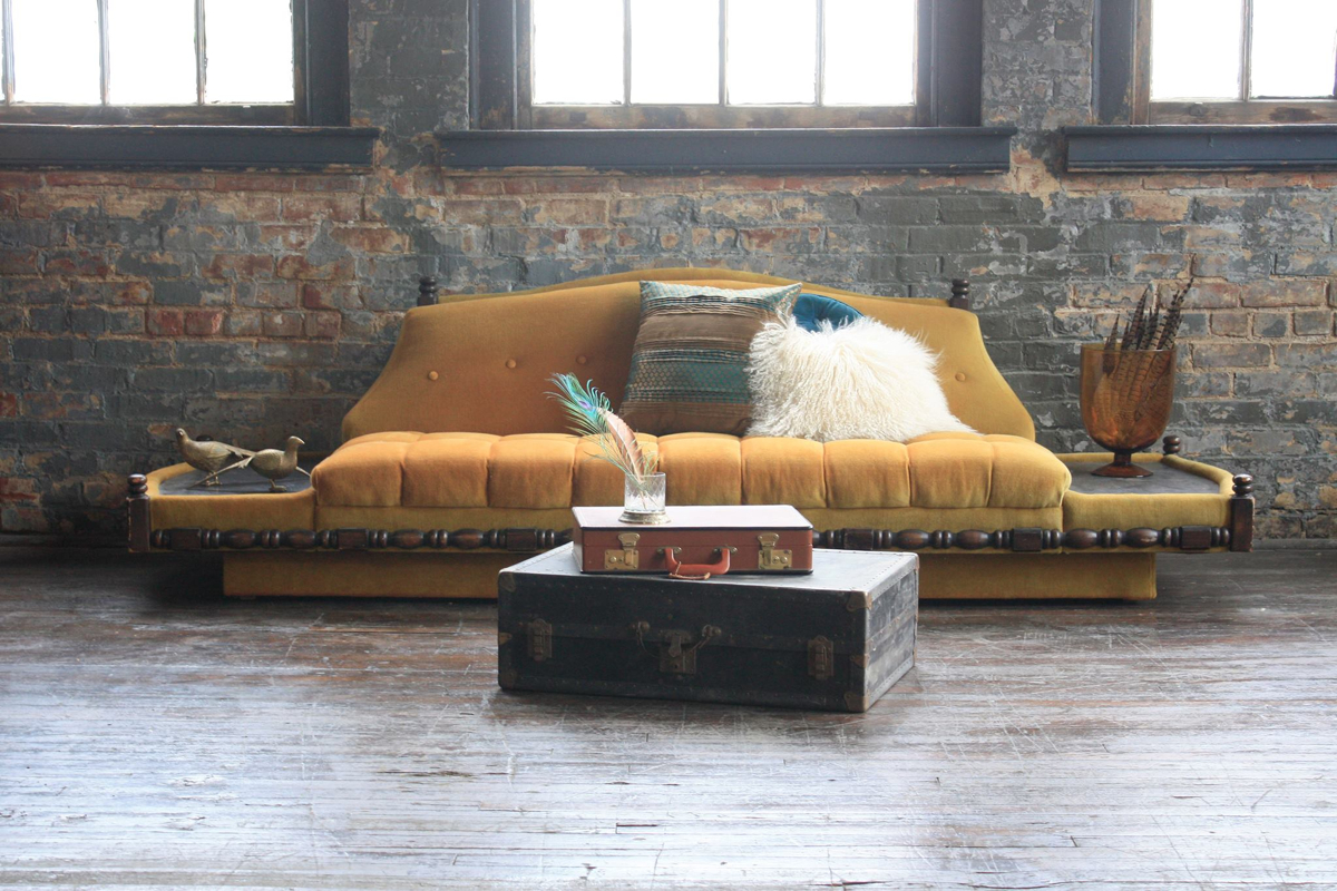 Meet Presley. This wacky guy has built-in end tables and lots of personality. Don't be fooled by that harvest gold. When styled just the right way, he can appear elegant and polished. Long and low, Presley is the perfect anchor piece for a Moroccan-style floor pillow lounge. -- Image courtesy of Queen City Vignette