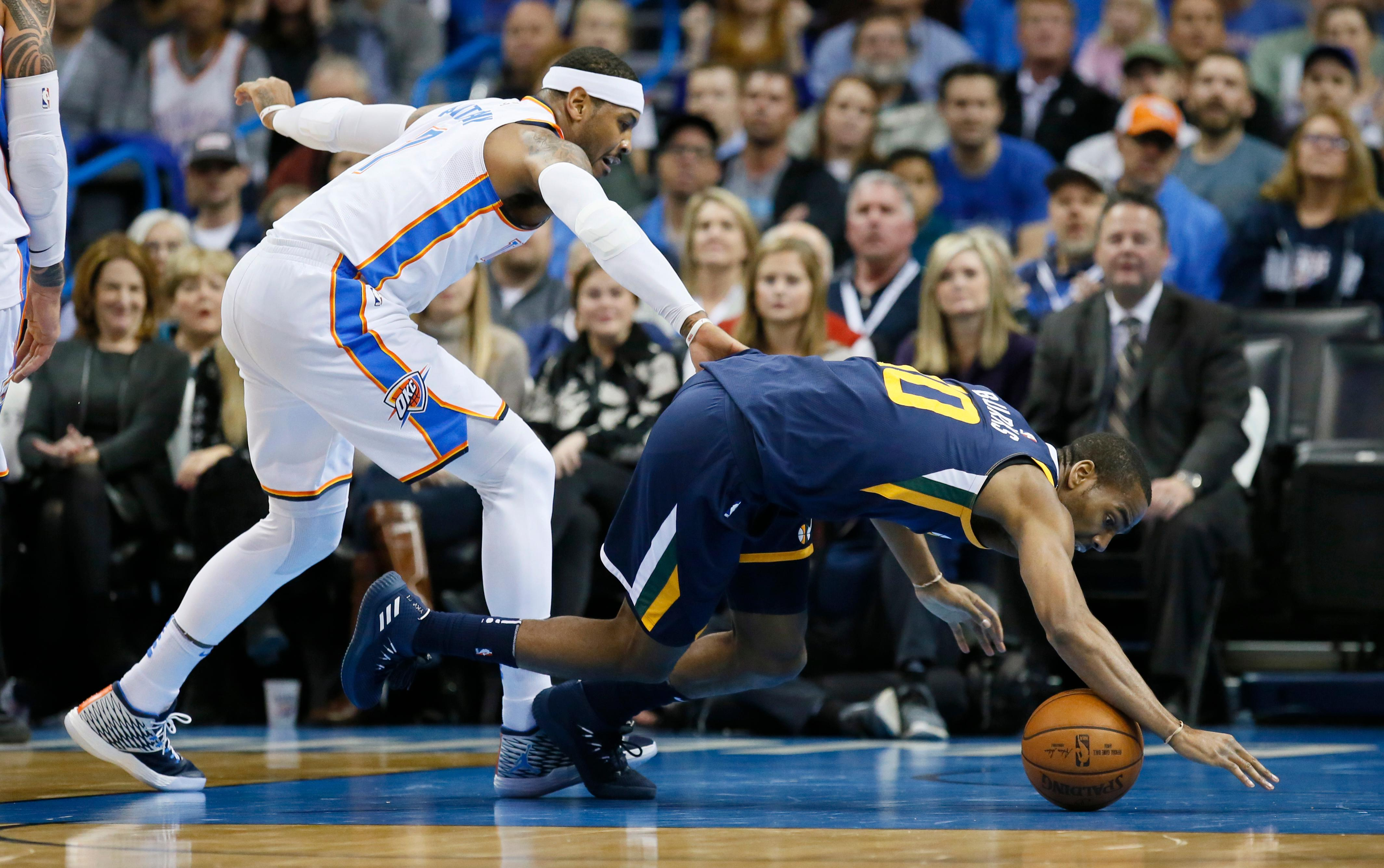 Utah Jazz guard Alec Burks (10) reaches for a loose ball in front of Oklahoma City Thunder forward Carmelo Anthony, left, in the first quarter of an NBA basketball game in Oklahoma City, Tuesday, Dec. 5, 2017. (AP Photo/Sue Ogrocki)