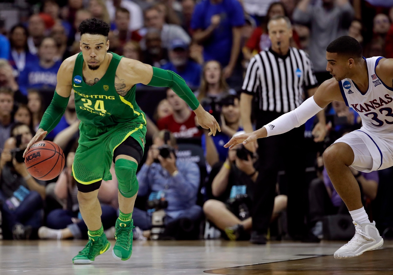 Oregon forward Dillon Brooks drives up the court past Kansas forward Landen Lucas, right, during the second half of the Midwest Regional final of the NCAA men's college basketball tournament, Saturday, March 25, 2017, in Kansas City, Mo. (AP Photo/Charlie Riedel)