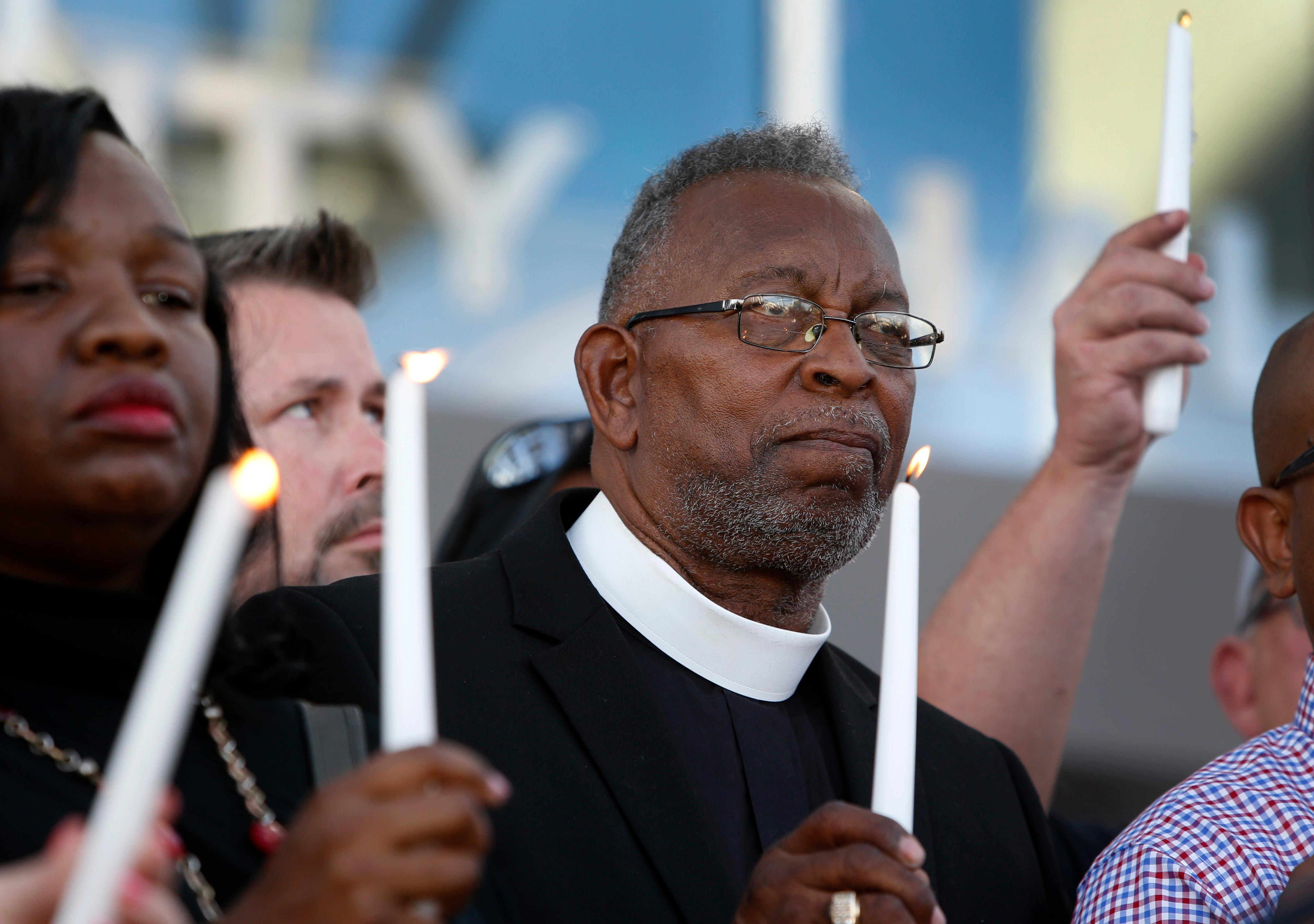 Pastor William McCurdy holds a candle during a prayer vigil in honor of those affected by the shooting on the Las Vegas Strip, in front of Las Vegas City Hall in Las Vegas, Monday, Oct. 2, 2017. The vigil was held in honor of the over 50 people killed and hundreds injured in a mass shooting at an outdoor music concert late Sunday. (Steve Marcus/Las Vegas Sun via AP)