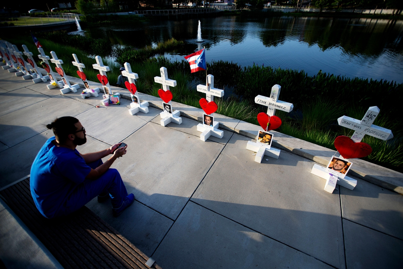 Ernesto Vergne looks at a cross honoring his friend Xavier Emmanuel Serrano Rosado and the other victims at a memorial to those killed in the Pulse nightclub mass shooting a few blocks from the club early Friday, June 17, 2016, in Orlando, Fla. (AP Photo/David Goldman)