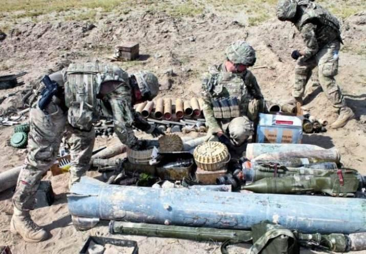 U.S. Army Spcs. Christopher McLaughlin, left, and Zachary Dechant, center, and U.S. Air Force Staff Sgt. William Voorhies place munitions on a pile to prepare for a controlled detonation on a range near Bagram Airfield, Afghanistan.