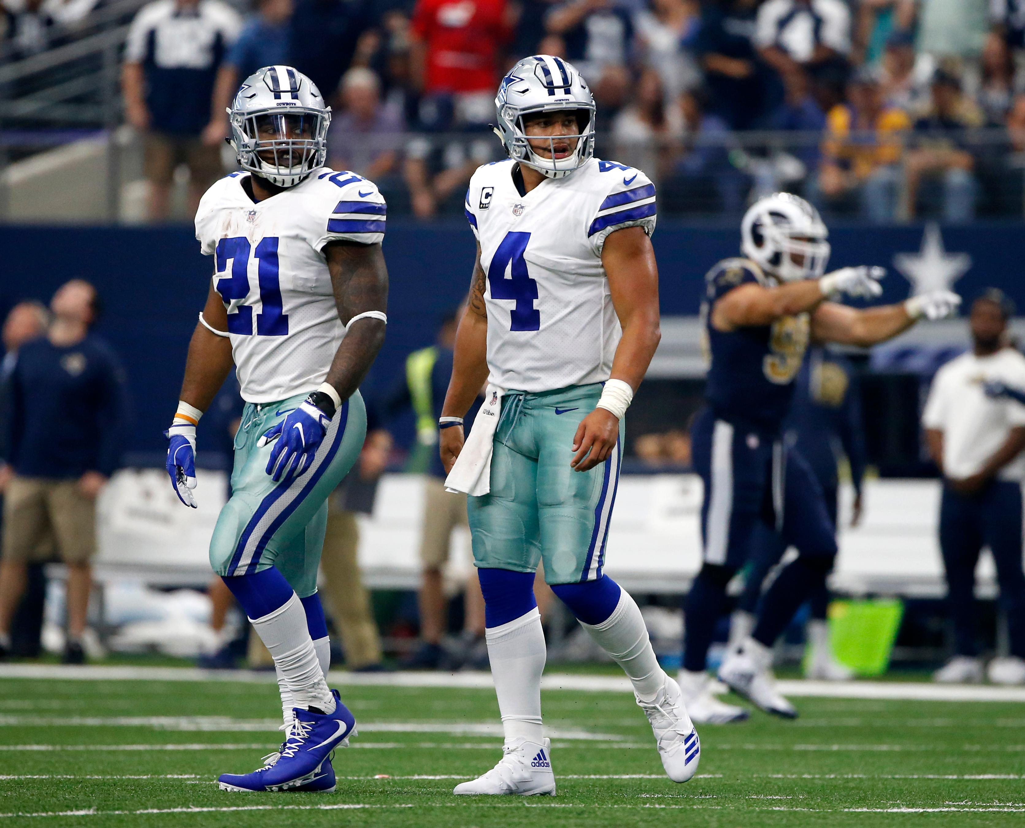 Dallas Cowboys running back Ezekiel Elliott (21) and quarterback Dak Prescott (4) walk off the field after an unsuccessful two-point conversion attempt on a pass to wide receiver Terrance Williams in the second half of an NFL football game against the Los Angeles Rams on Sunday, Oct. 1, 2017, in Arlington, Texas. (AP Photo/Ron Jenkins)