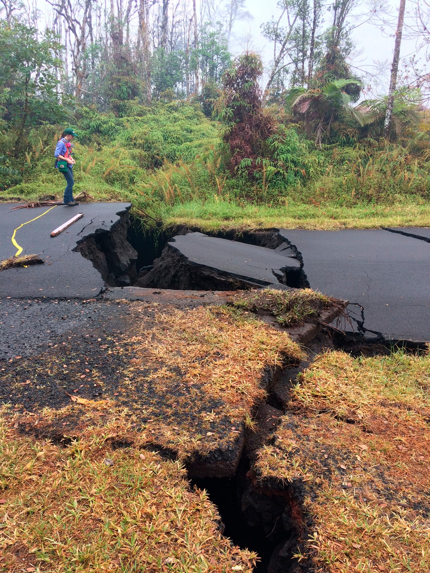 In this Thursday, May 17, 2018 image released by the U.S. Geological Survey, a Hawaiian Volcano Observatory, HVO geologist monitors the the vertical offset across the cracks on Nohea Street in Leilani Estates in Pahoa, Hawaii. Cracks caused by the underlying intrusion of magma expanded significantly during the past 24 hours, some with horizontal and vertical offsets, into the lower East Rift Zone in the Big Island of Hawaii. (U.S. Geological Survey via AP)
