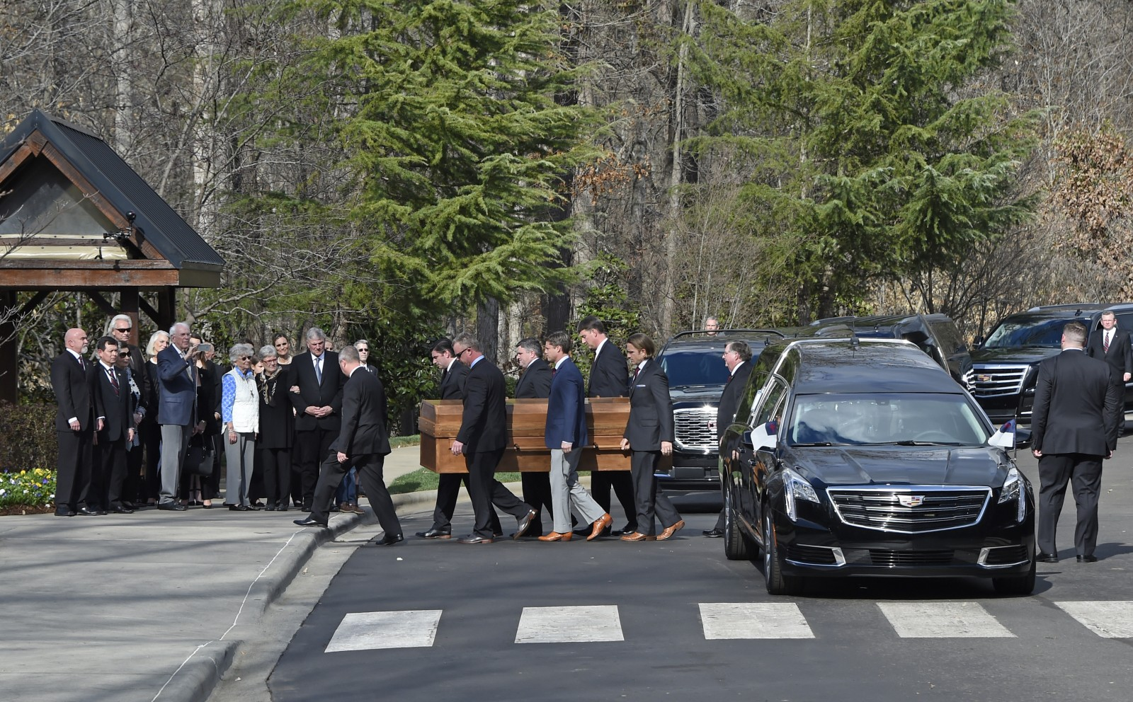 Pallbearers carry the casket with the body of Billy Graham past family members as it arrives at the Billy Graham Library in Charlotte, N.C., Saturday, Feb. 24, 2018. (Kathy Kmonicek/pool photo)