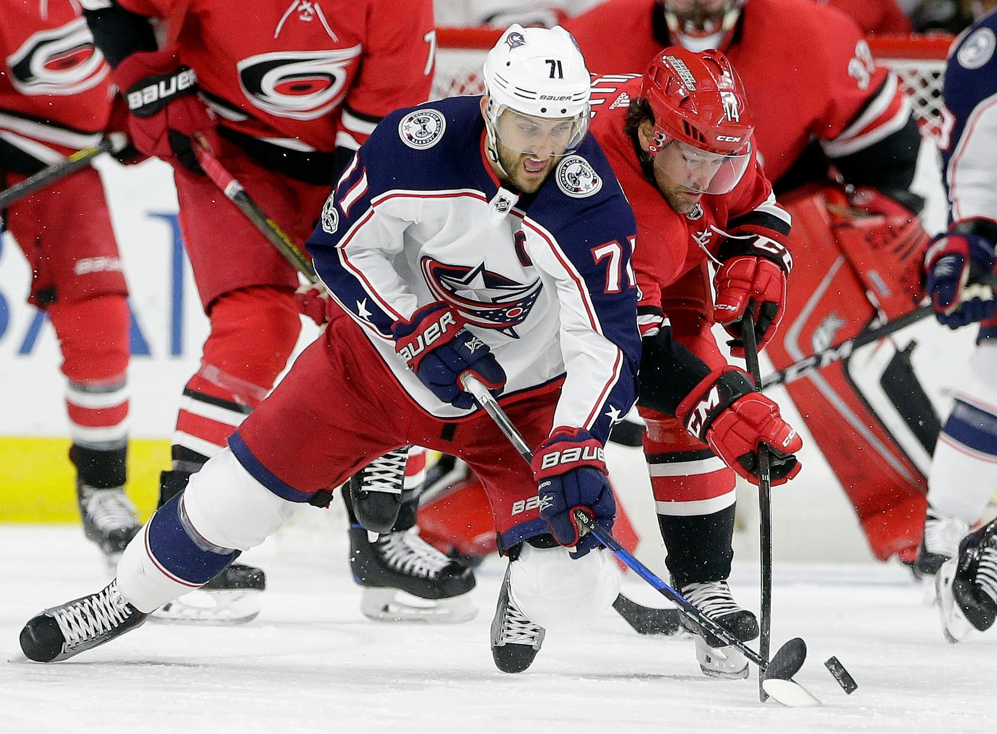 Columbus Blue Jackets' Nick Foligno (71) and Carolina Hurricanes' Justin Williams (14) chase the puck during the second period of an NHL hockey game in Raleigh, N.C., Tuesday, Oct. 10, 2017. (AP Photo/Gerry Broome)
