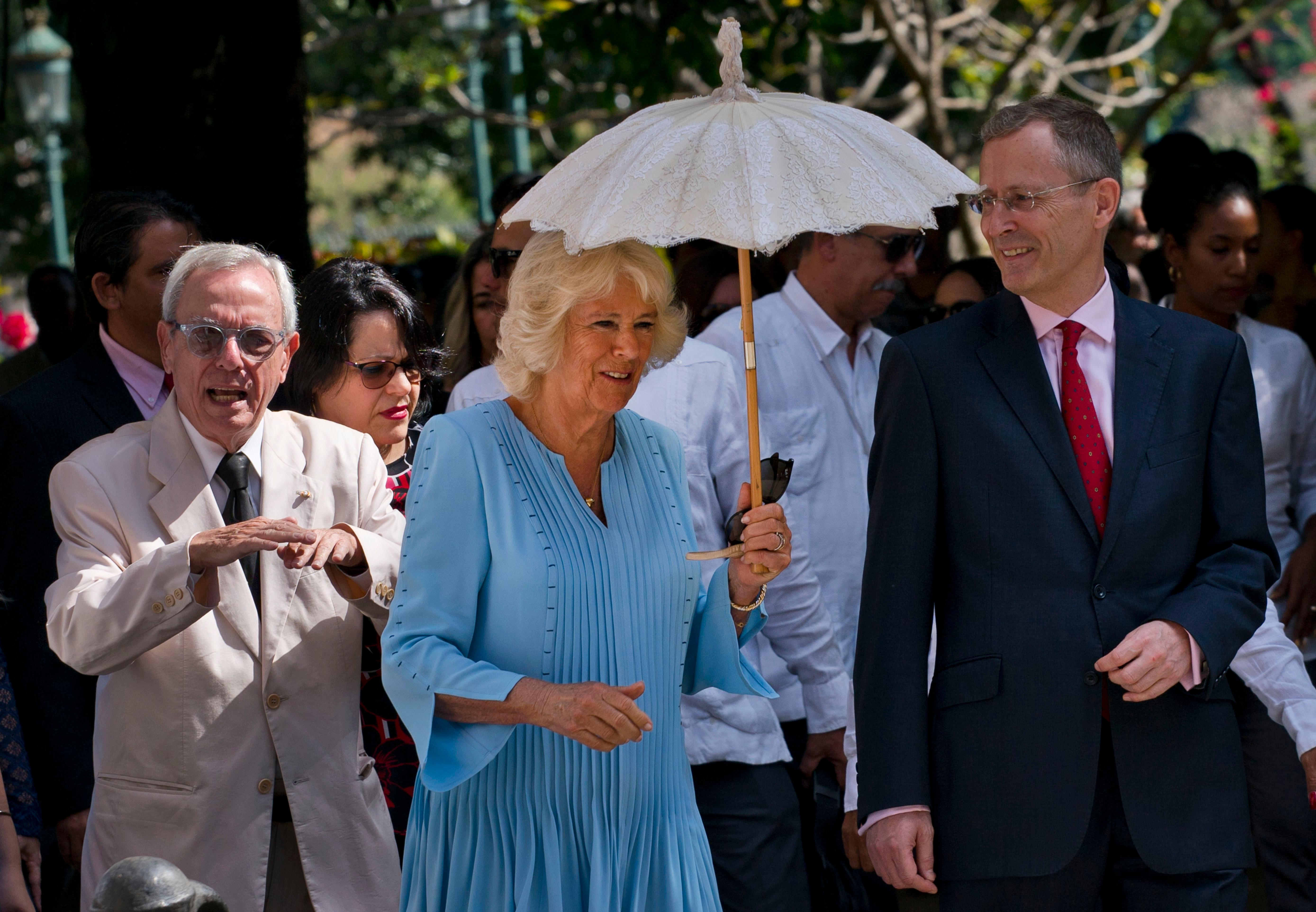 Camilla, Duchess of Cornwall, shades herself with an umbrella during a guided tour of Old Havana by City Historian Eusebio Leal, left, in Havana, Cuba, Monday, March 25, 2019. (AP Photo/Ramon Espinosa)