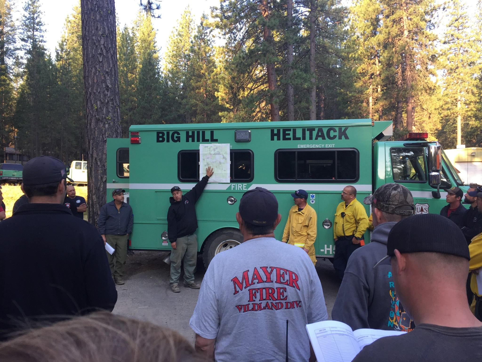 Steve Tolen, Operations Chief (hand on map) and Leon Jeffrey, Incident Commander (to left of Tolen) conducting morning briefing for firefighters. (Courtesy: U.S. Forest Service-Plumas National Forest)