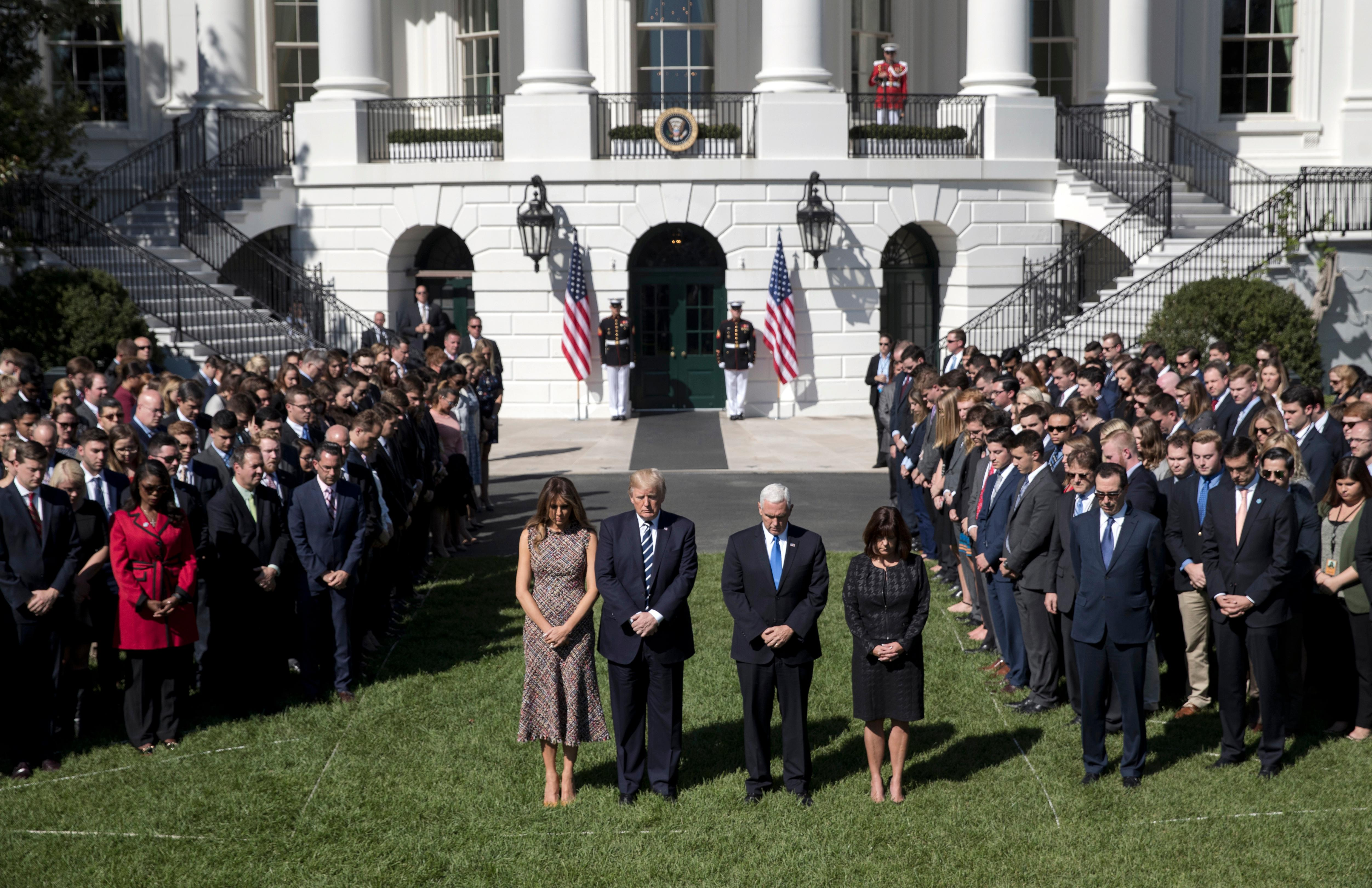 President Donald Trump and first lady Melania Trump stand with Vice President Mike Pence, his wife Karen, and members of the White House staff during a moment of silence to remember the victims of the mass shooting in Las Vegas, on the South Lawn of the White House in Washington, Monday, Oct. 2, 2017. (AP Photo/Carolyn Kaster)