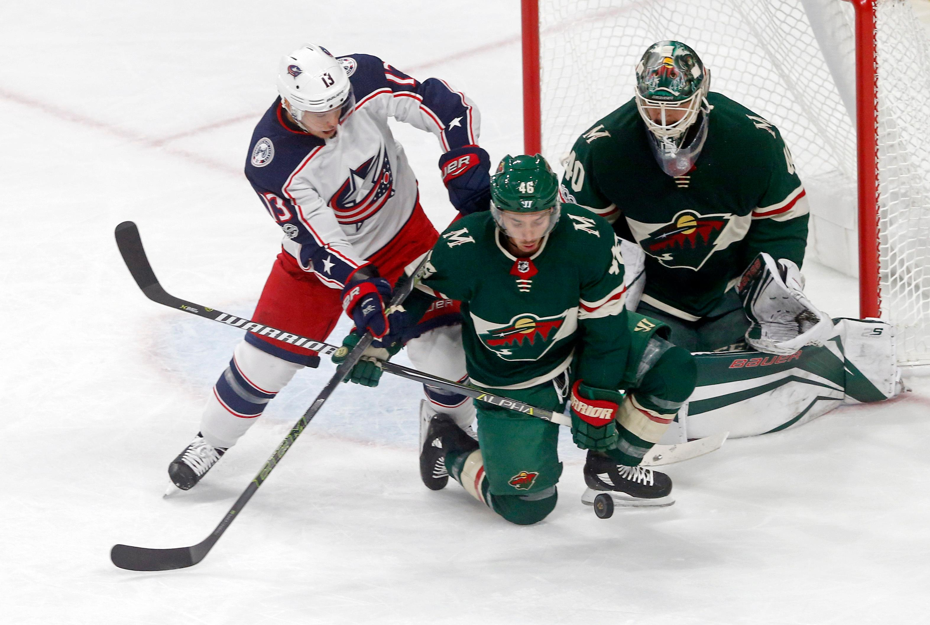 Minnesota Wild's Jared Spurgeon, center, tries to keep Columbus Blue Jackets' Cam Atkinson, left, away from the puck as Wild goalie Devan Dubnyk, right, defends the net during the first period of an NHL hockey game Saturday, Oct. 14, 2017, in St. Paul, Minn. (AP Photo/Jim Mone)