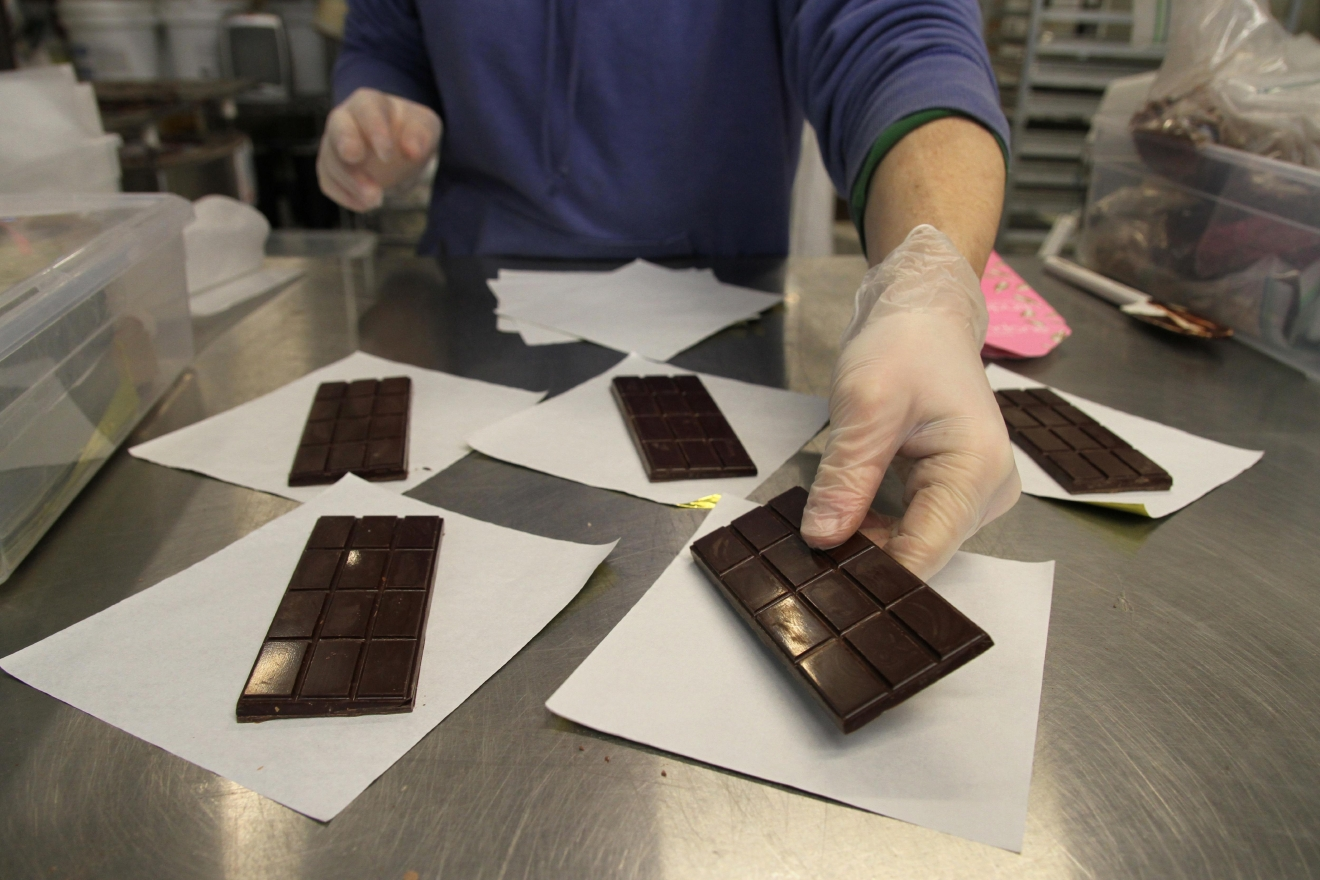 Adam lays out several chocolate bars that have pink Himalayan salt. (Image: Amanda Andrade-Rhoades/ DC Refined)