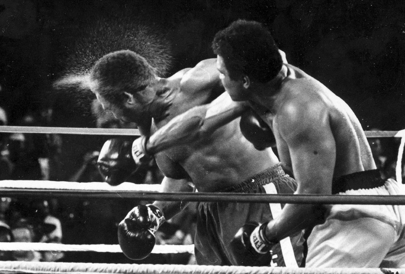 This is a Oct. 30, 1974, file photo showing George Foreman taking a right to the head from challenger Muhammad Ali in the seventh round in the match dubbed Rumble in the Jungle in Kinshasa, Zaire. Ali, the magnificent heavyweight champion whose fast fists and irrepressible personality transcended sports and captivated the world, has died according to a statement released by his family Friday, June 3, 2016. He was 74. (AP Photo/Ed Kolenovsky, File)