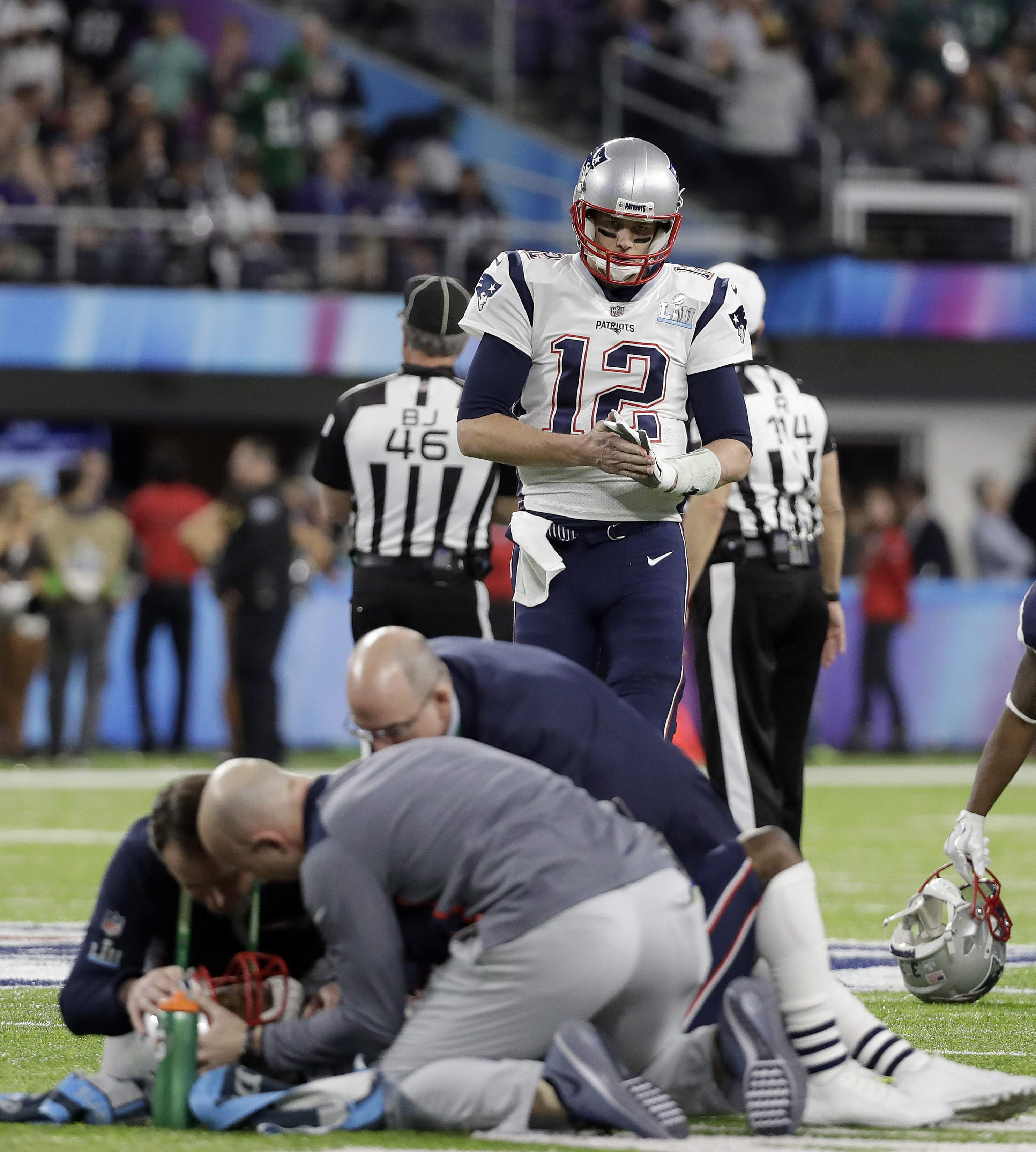 New England Patriots quarterback Tom Brady (12) looks as Brandin Cooks, bottom, is tended to after being hit during the first half of the NFL Super Bowl 52 football game against the Philadelphia Eagles Sunday, Feb. 4, 2018, in Minneapolis. (AP Photo/Mark Humphrey)