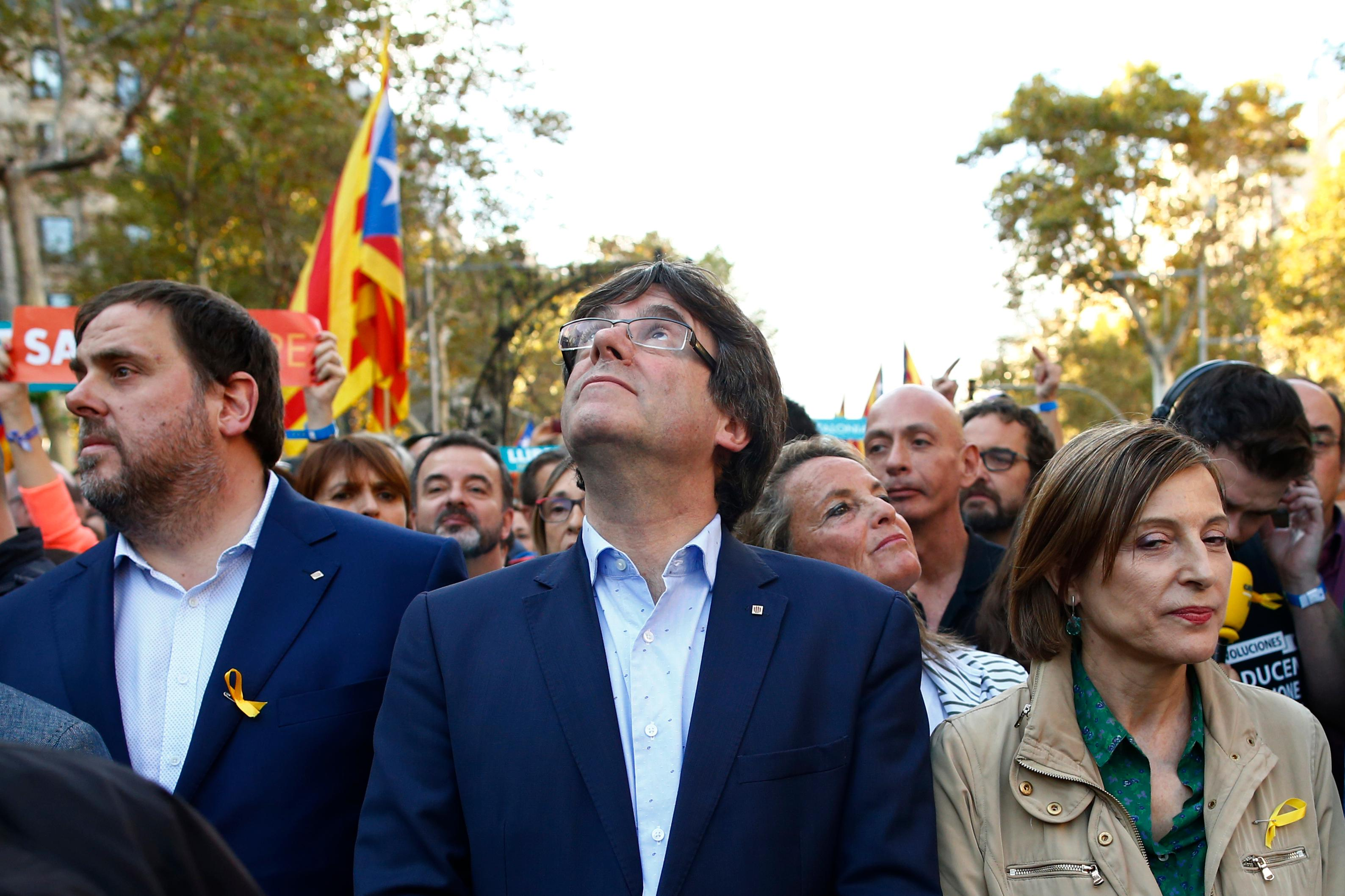 Catalan President Carles Puigdemont, centre, takes part at a march with deputy president Oriol Junqueras, left and Carme Forcadell, speaker of the house in the Catalan parliament to protest against the National Court's decision to imprison civil society leaders, in Barcelona, Spain, Saturday, Oct. 21, 2017. The Spanish government moved decisively Saturday to use a previously untapped constitutional power so it can take control of Catalonia and derail the independence movement led by separatist politicians in the prosperous industrial region. (AP Photo/Manu Fernandez)