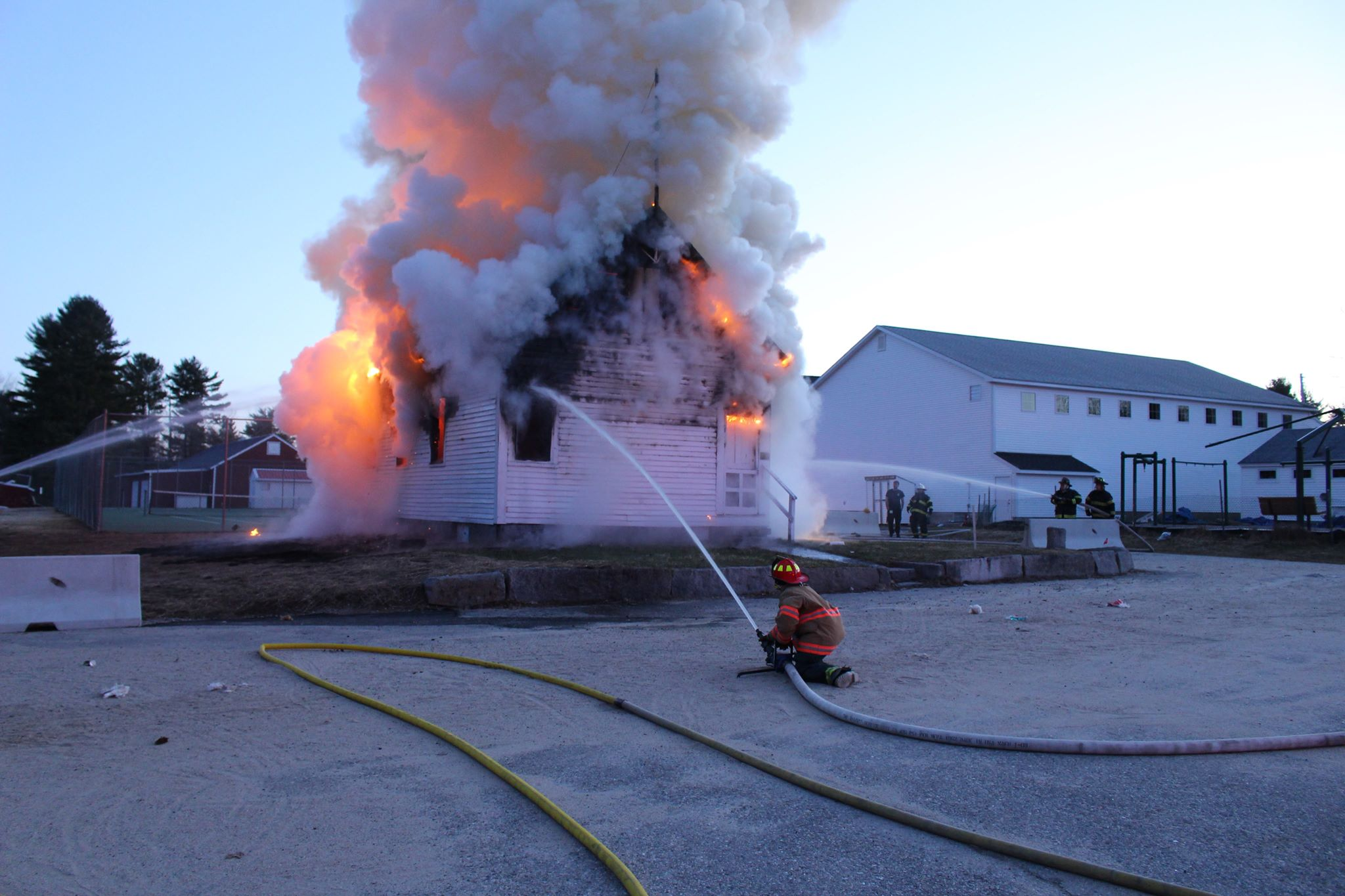 Junior firefighter Jordan Magiera mans a fire hose atThe Old School House in Cascom which heavily damaged in an early morning fire Sunday. (Lisa Magiera)