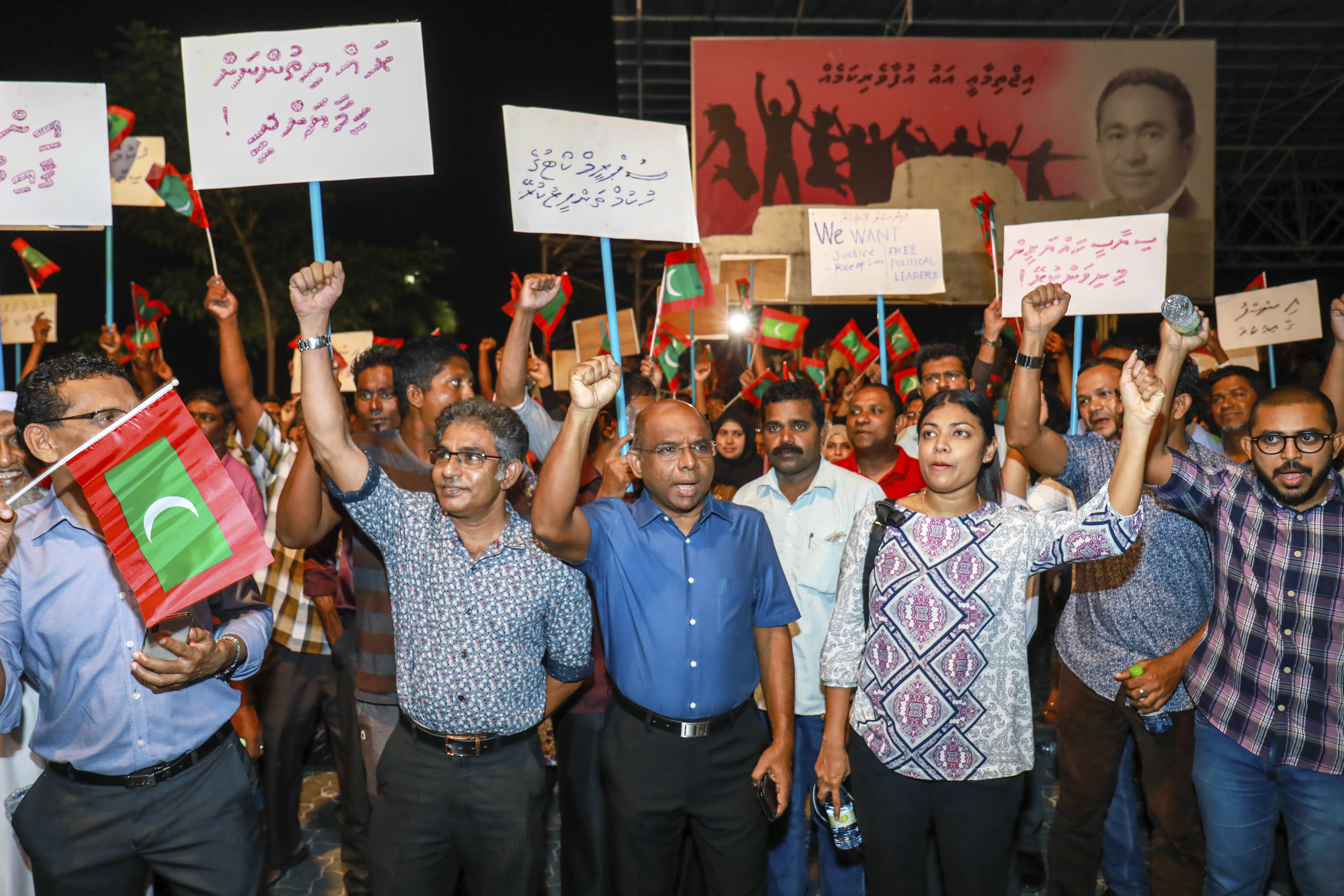 "In this late Sunday, Feb.4, 2018 photo, Maldivian opposition supporters shout slogans during a protest as they the urge the government to obey a Supreme Court order to release and retry political prisoners, including an ex-president in Male, Maldives. The political crisis in the Maldives deepened Monday, as the government of the island nation said it would not obey a Supreme Court order to free a group of imprisoned opposition leaders. Placards in Divehi language from left, to right, read, ""protect the citizens , carry out the supreme court's order, free political prisoners and to uphold justice"". (AP Photo/ Mohamed Sharuhaan)"