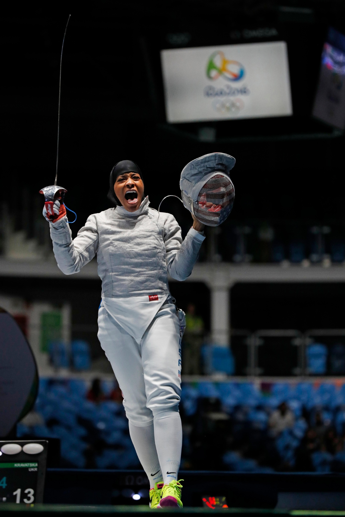 Ibtihaj Muhammad, from the United States, celebrates defeating Olena Kravatska, from Ukraine, during the women's saber individual fencing event at the 2016 Summer Olympics in Rio de Janeiro, Brazil, Monday, Aug. 8, 2016. (AP Photo/Vincent Thian)