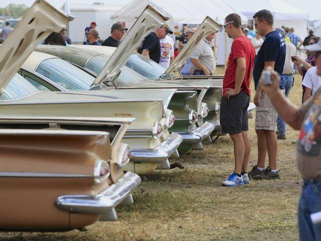 Potential bidders look over vintage 1959 Chevrolets lined up in a field near the former Lambrecht Chevrolet car dealership in Pierce, Neb.