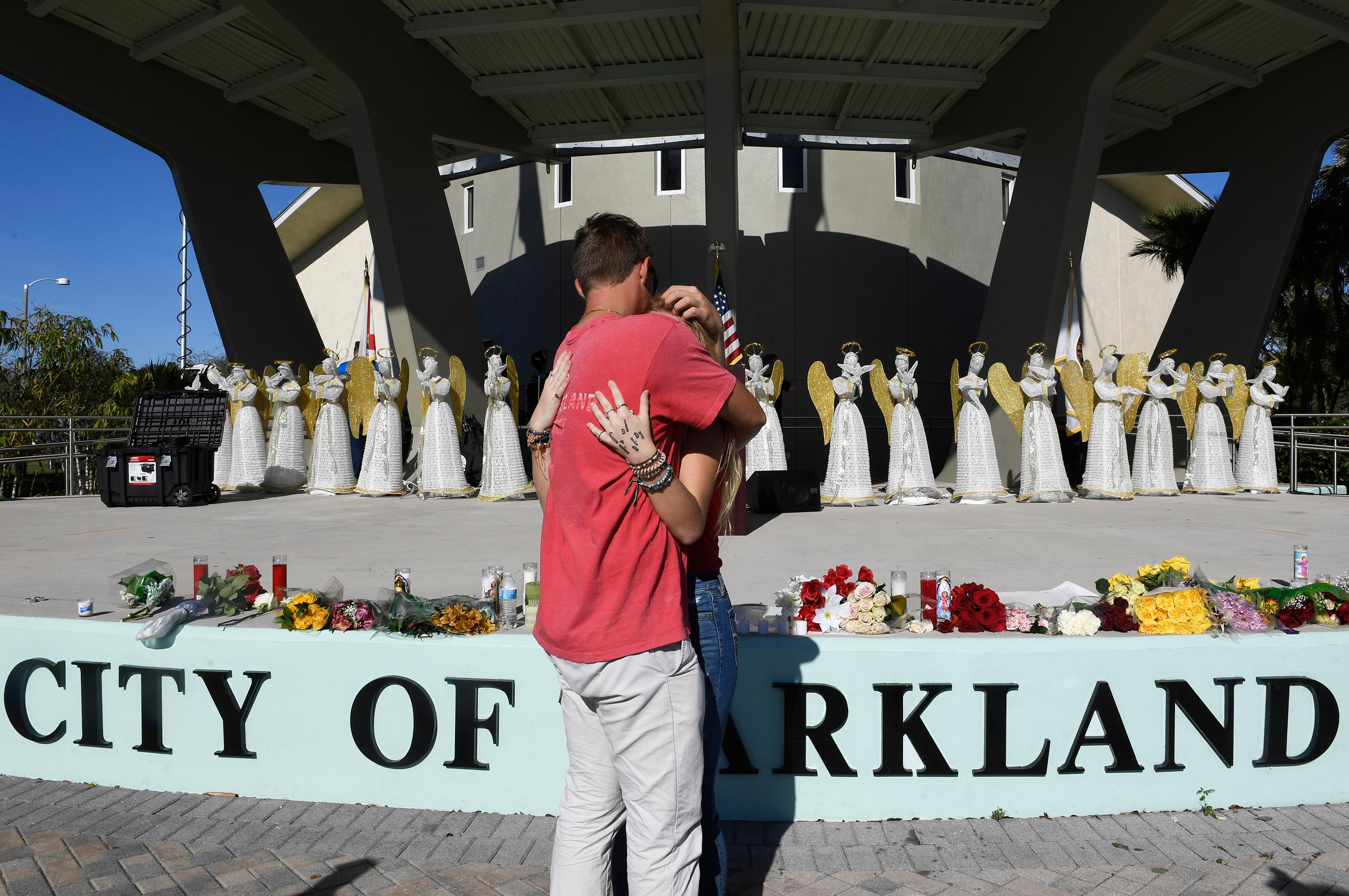 Zack King, left, comforts friend Mychal Bradley in front of 17 angels representing those who died in Wednesday's shooting at Marjory Stoneman Douglas High School Thursday, Feb. 15, 2018, in Parkland, Fla. The teenager accused of using a semi-automatic rifle to kill more than a dozen people and injuring others at a Florida high school confessed to carrying out one of the nation's deadliest school shootings and concealing extra ammunition in his backpack, according to a sheriff's department report released Thursday. (Taimy Alvarez/South Florida Sun-Sentinel via AP)