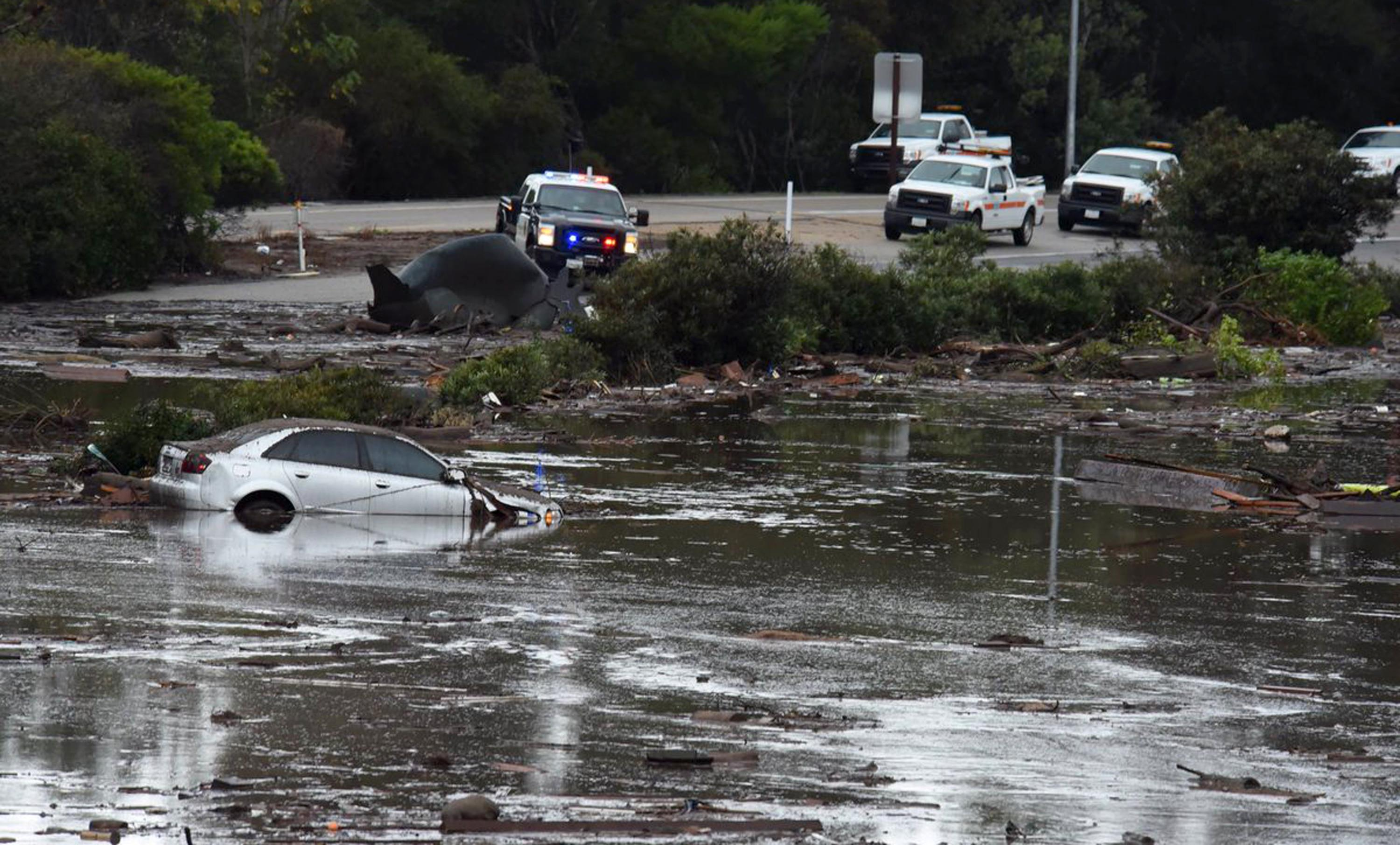 This photo provided by the Santa Barbara County Fire Department shows the U.S. Highway 101 at the Olive Mill Road overpass flooded with runoff water from Montecito Creek in Montecito, Calif., Tuesday, Jan. 9, 2018. Dozens of homes were swept away or heavily damaged Tuesday as downpours sent mud and boulders roaring down hills stripped of vegetation by a gigantic wildfire that raged in Southern California last month. (Mike Eliason/Santa Barbara County Fire Department via AP)
