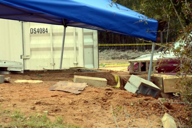 A tent covers the bunker where a 5-year-old child was rescued by law enforcement after being held for nearly a week. FBI agents placed the blue tent over the bunker to protect evidence below.