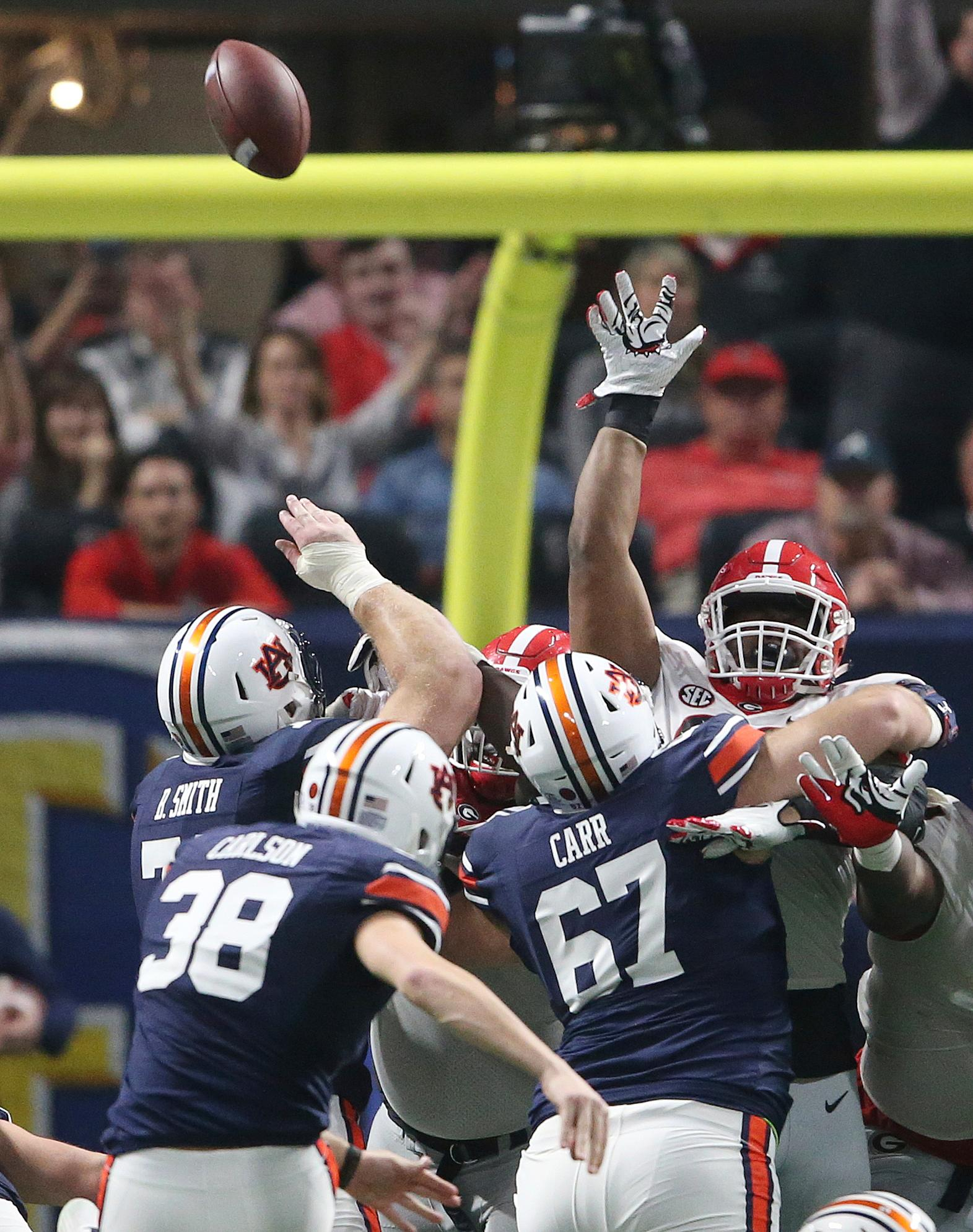 Georgia defensive tackle DaQuan Hawkins-Muckle , right, blocks a field goal attempt by Auburn place kicker Daniel Carlson (38) during the second half of the Southeastern Conference championship NCAA college football game, Saturday, Dec. 2, 2017, in Atlanta. Georgia safety Dominick Sanders picked up the ball. (AP Photo/John Bazemore)