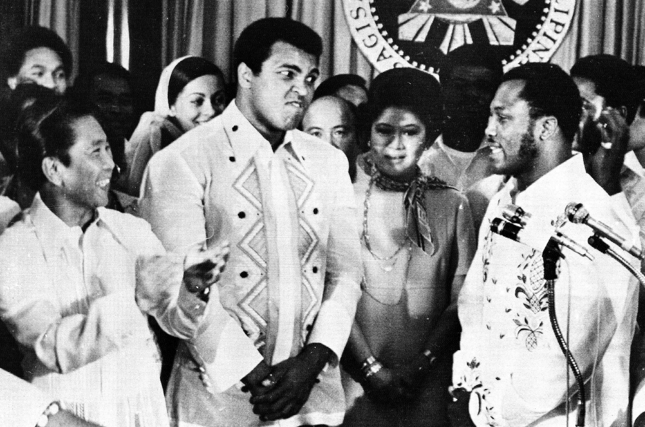 In this Sept. 18, 1975, file photo, Philippines President Ferdinand Marcos, left, applauds as challenger Joe Frazier, right, makes some remarks about world champion Muhammad Ali, second from left, during their call on Marcos at the Malacanang Palace in Manila, Philippines. Ali, the magnificent heavyweight champion whose fast fists and irrepressible personality transcended sports and captivated the world, has died according to a statement released by his family Friday, June 3, 2016. He was 74. (AP Photo/Jess Tan, File)