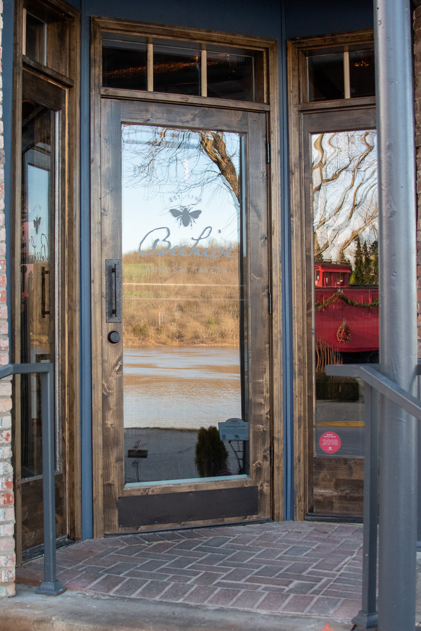 "A muddy Ohio River reflects off of the glass entryway to The Beehive Tavern, commonly referred to as ""The Beehive"". / Image: Matt Groves // Published: 2.23.20"