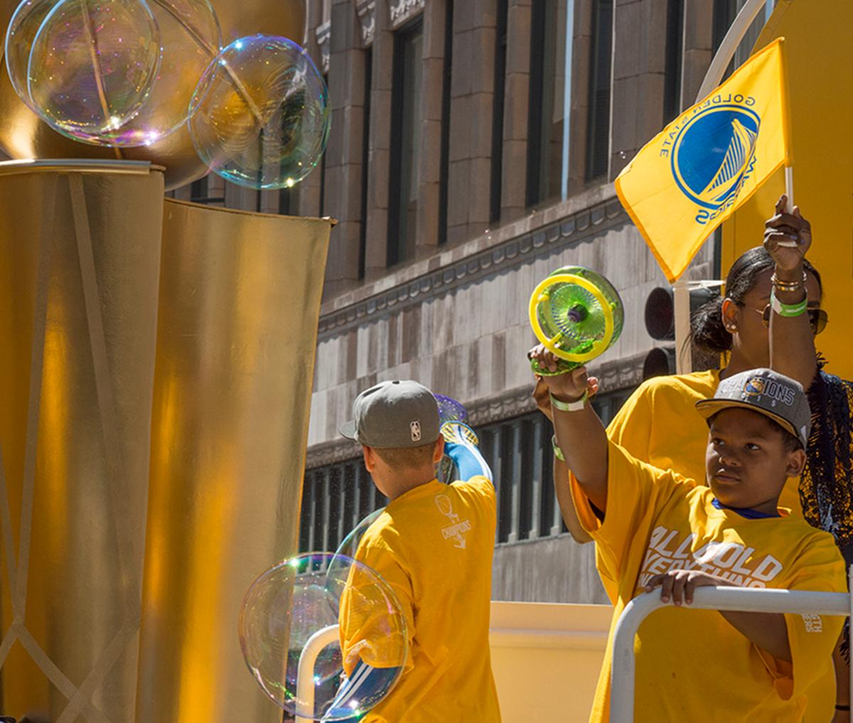 Oakland community members blow bubbles and wave to the crowd atop a float in the Golden State Warriors victory parade. Photo by Emily Gonzalez, Oregon News Lab.