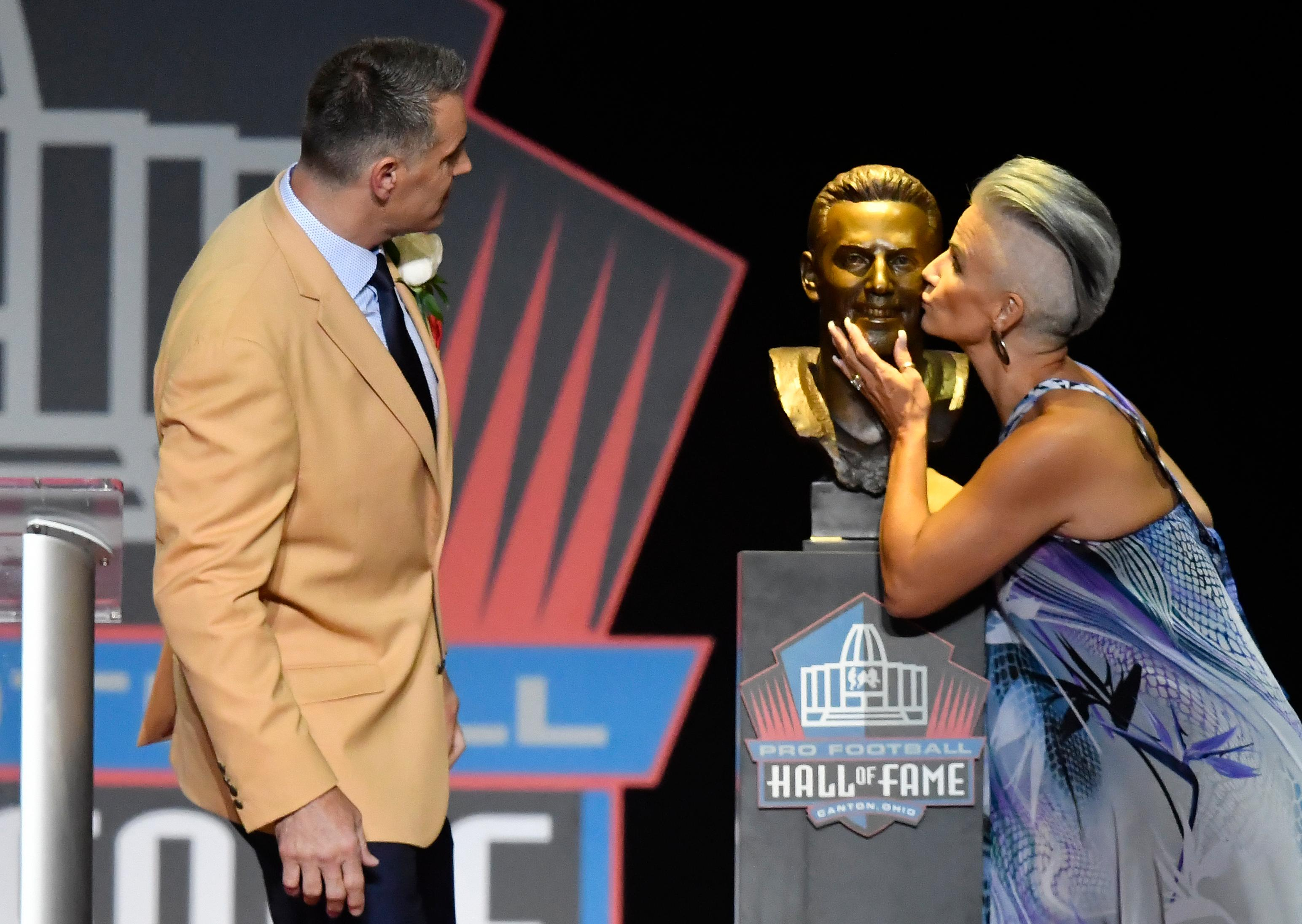 Former NFL quarter Kurt Warner, left, watches as his wife and presenter, Brenda Warner, kisses a bust of him before his speech during inductions at the Pro Football Hall of Fame on Saturday, Aug. 5, 2017, in Canton, Ohio. (AP Photo/David Richard)