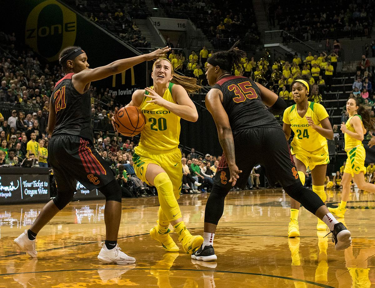 Oregon Ducks Sabrina Ionescu (#20) attempts to make her way through USC Trojans defense. The Oregon Ducks defeated the USC Trojans 80-74 on Friday at Matthew Knight Arena in a game that went into double overtime. Lexi Bando sealed the Ducks' victory by scoring a three-pointer in the closing of the game. Ruthy Hebard set a new NCAA record of 30 consecutive field goals in three straight games, the old record being 28. Ruthy Hebard got a double-double with 27 points and 10 rebounds, Mallory McGwire also had 10 rebounds. The Ducks had four players in double digits. The Ducks are now 24-4, 13-2 in the Pac-12, and are tied for first with Stanford. Photo By Rhianna Gelhart, Oregon News Lab