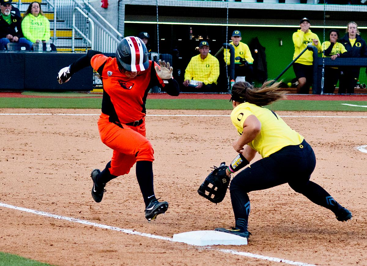 Oregon State Beavers Lovie Lopez (#29) beats the throw to Oregon Ducks first base player Mia Camuso (#7). The Oregon Ducks defeated the Oregon State Beavers 8-0 in game one of the three-game Civil War series on Friday night at Jane Sanders Stadium. The game was 0-0 until Gwen Svekis (#21) hit a solo homerun in the fourth inning. Mia Camuso hit a grand slam in the fifth inning, ending the game for the Ducks by mercy rule. Photo by Dan Morrison